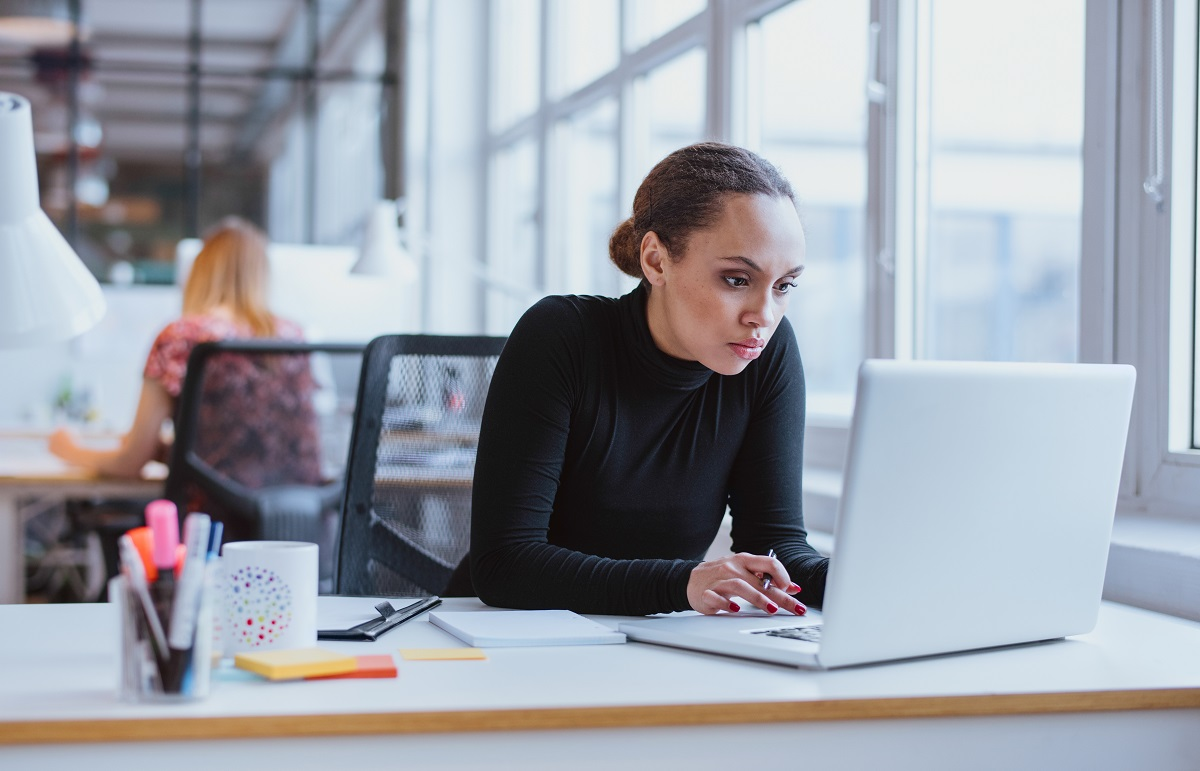 Woman sits at desk in windowed modern office, she is using a laptop with a focused expression on her face