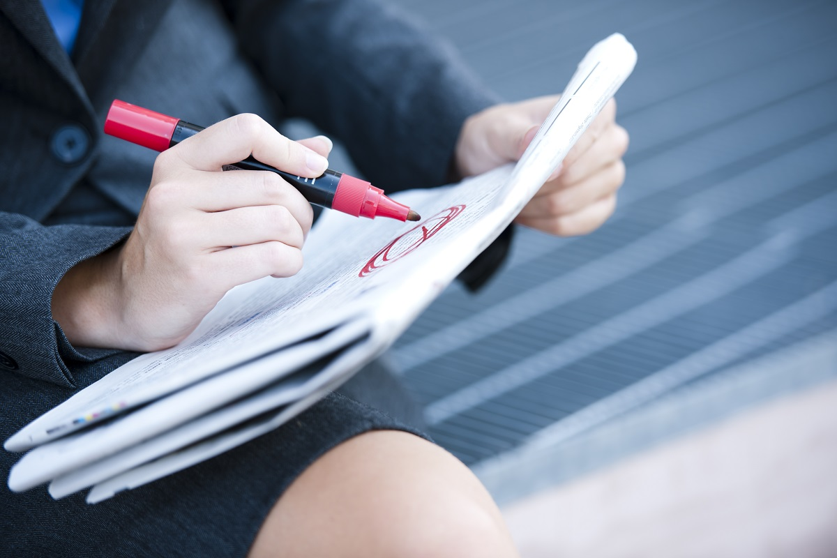 Unemployed woman looking for work circles newspaper opportunity in red marker