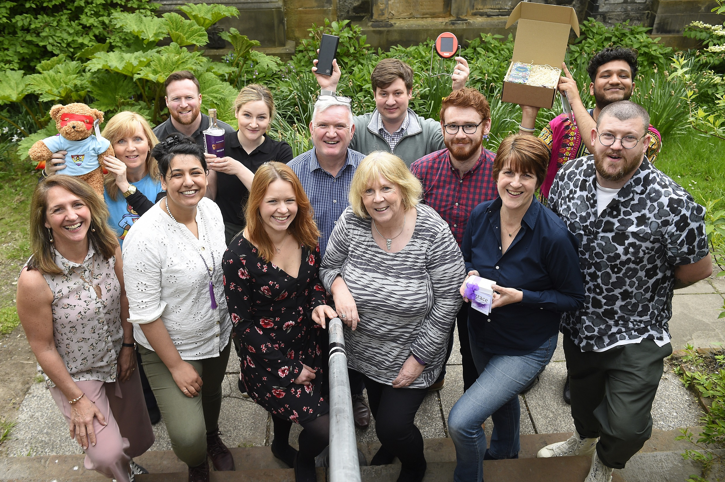 Attendees at the 2019 SIS Retail Academy gather for a photo, some are holding their retail products in the air such as a teddy bear and a bottle of alcohol