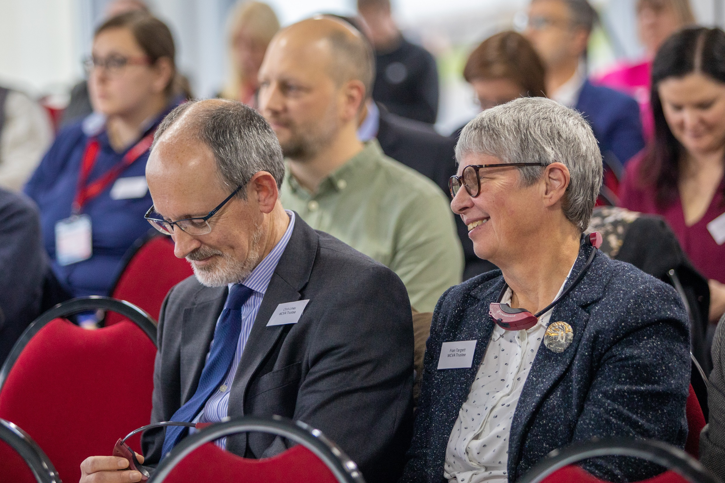 The audience at WCVA's AGM and Annual Lecture 2019. People are sat in rows and a man an woman at the forefront of the photo are smiling