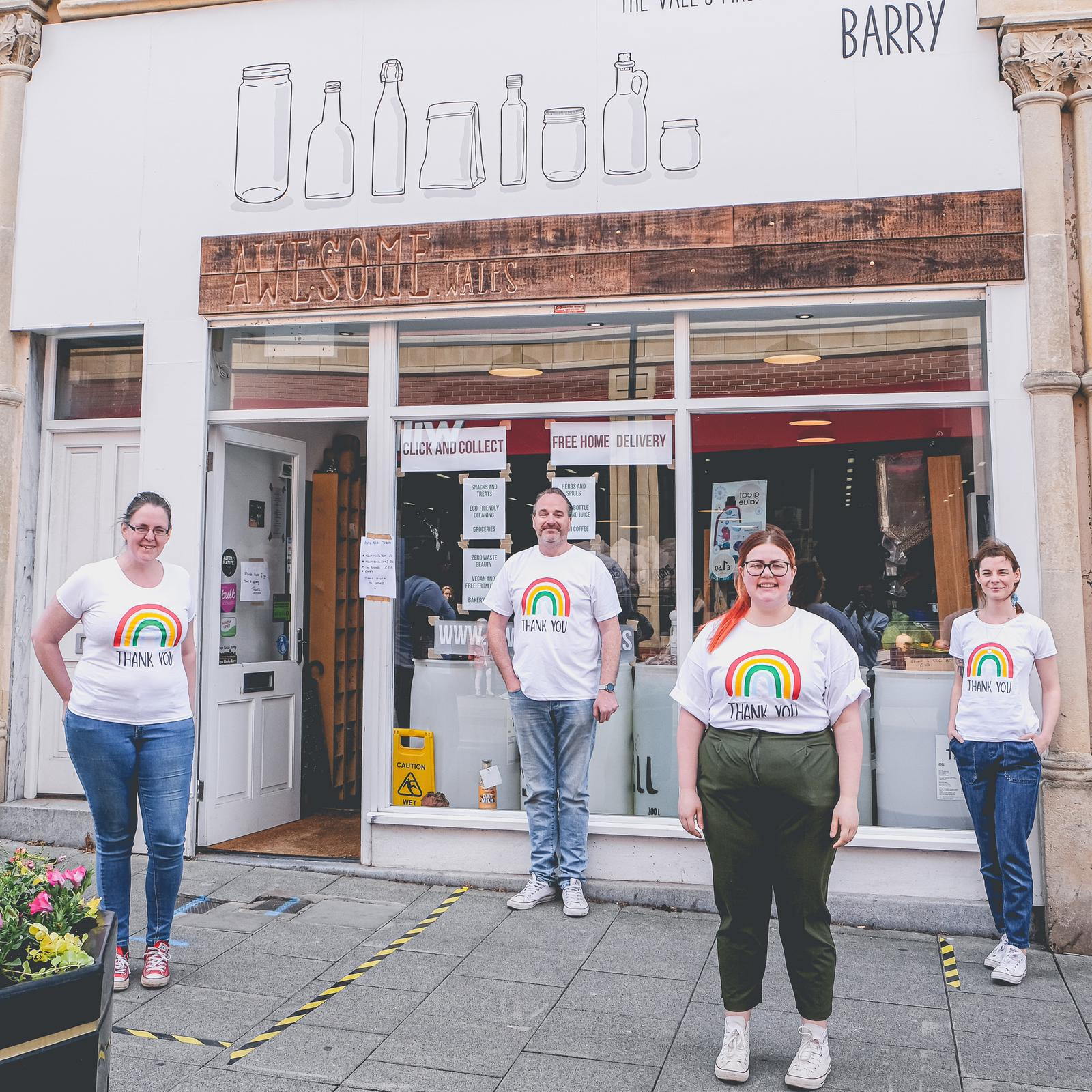 Awesome Wales staff stand outside the store front in NHS rainbow t-shirts