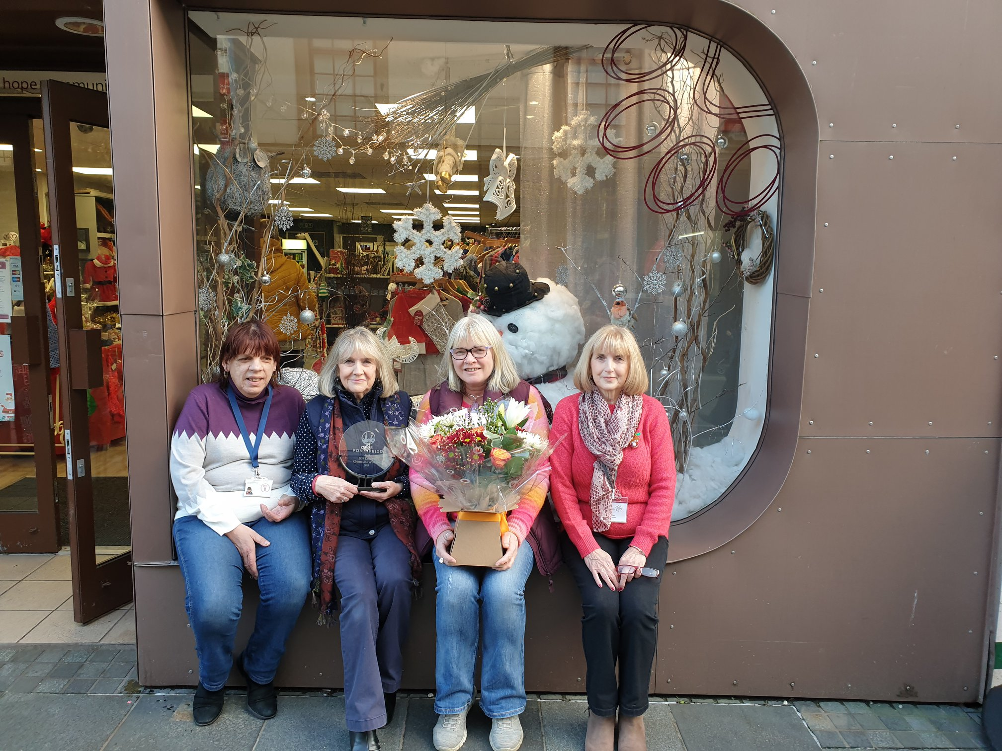 Hope Rescue charity shop staff sit in front of a shop window filled with Christmas decorations