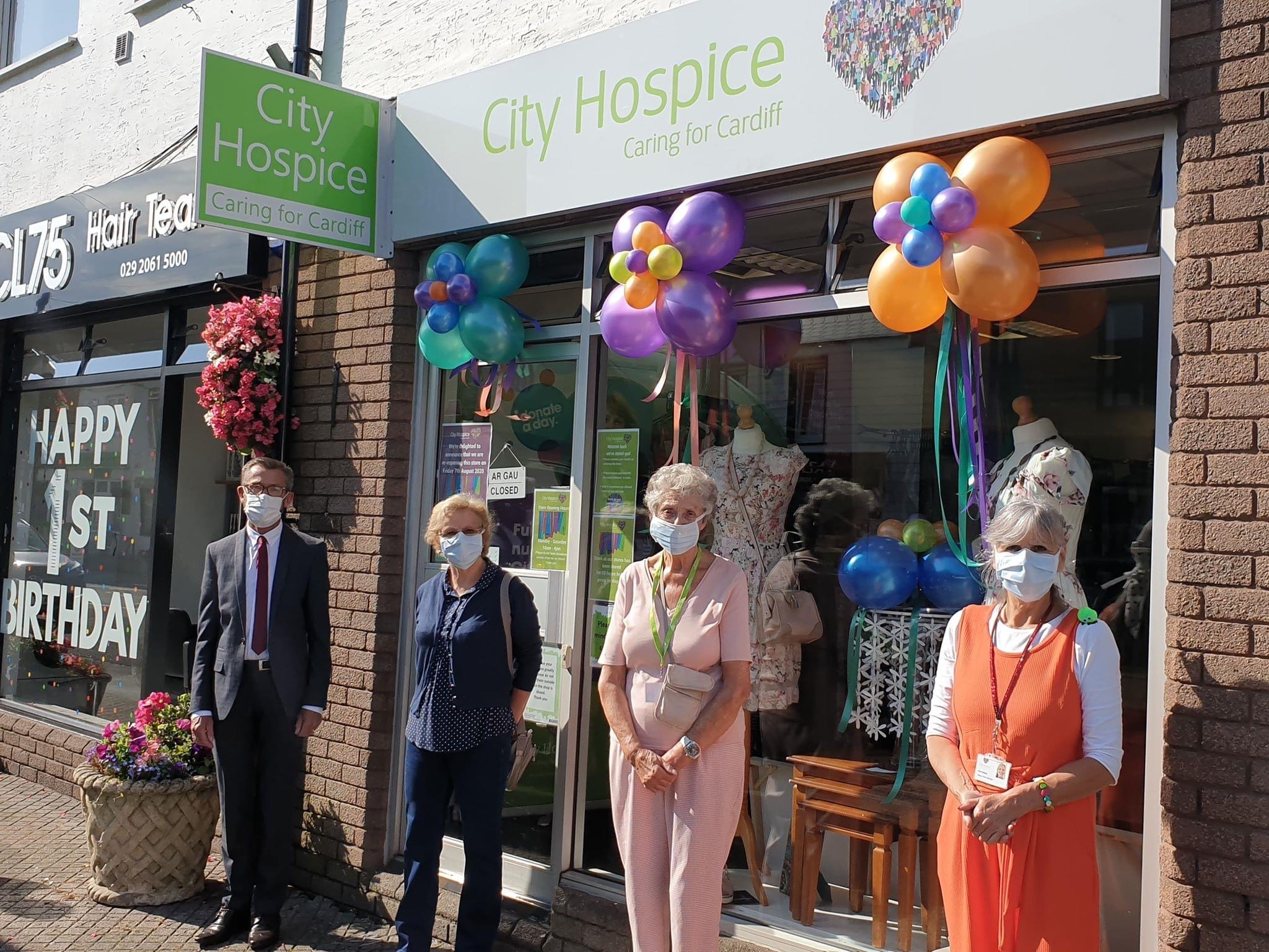 Volunteers stand socially distanced outside City Hospice Caring for Cardiff charity shop, they are wearing face masks and the shop front has colourful balloons decorating it
