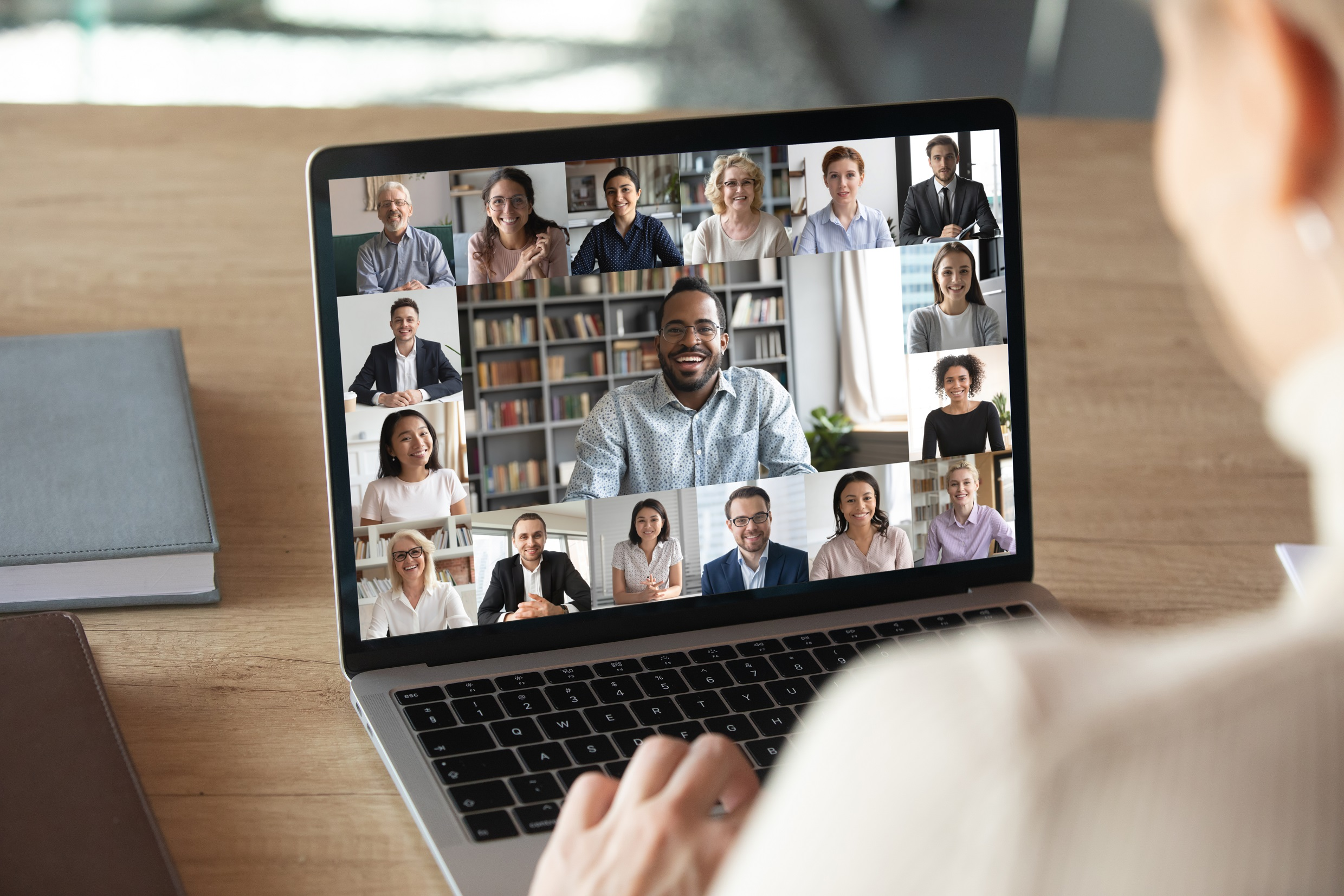 Over the should view of a person on a laptop, the screen shows a video call with a diverse range of people