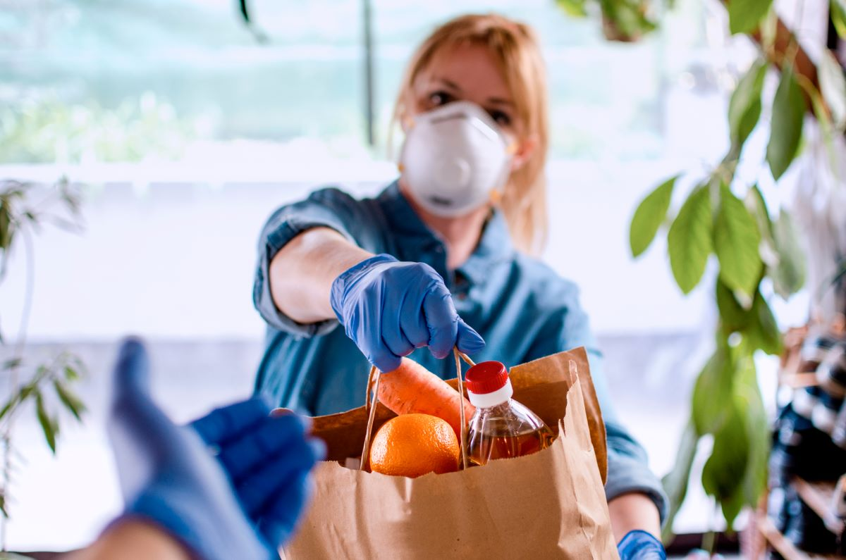 A woman in a mask hands over a bag of food