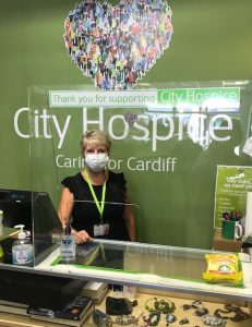 Masked volunteer stands behind the ill in charity shop
