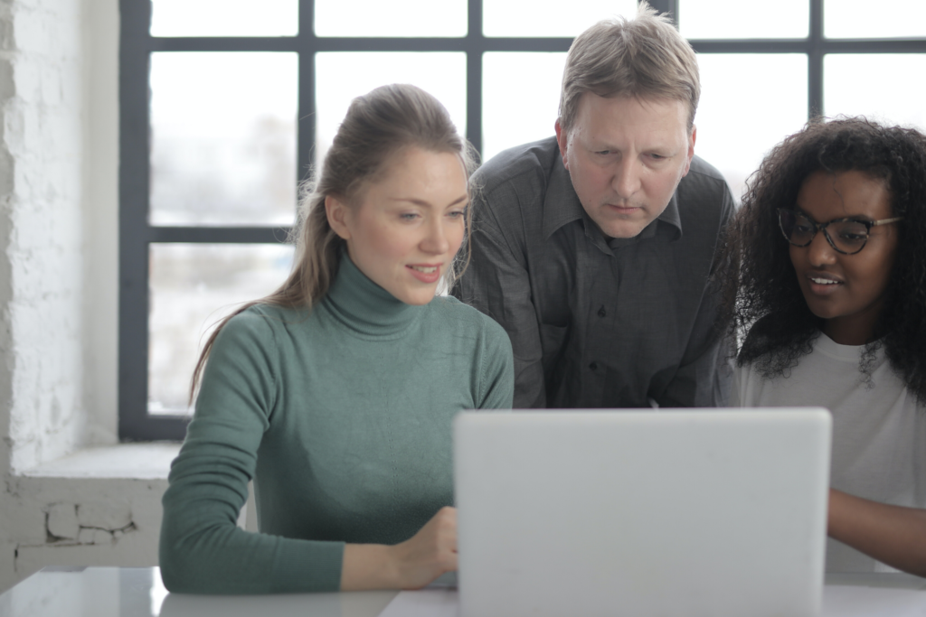 Group of people huddled around laptop looking at knowledge hub