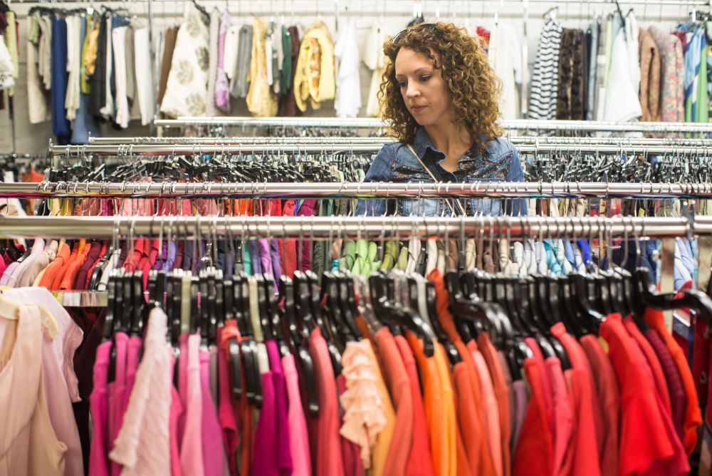 A woman volunteer sorting colourful clothes at a charity shop