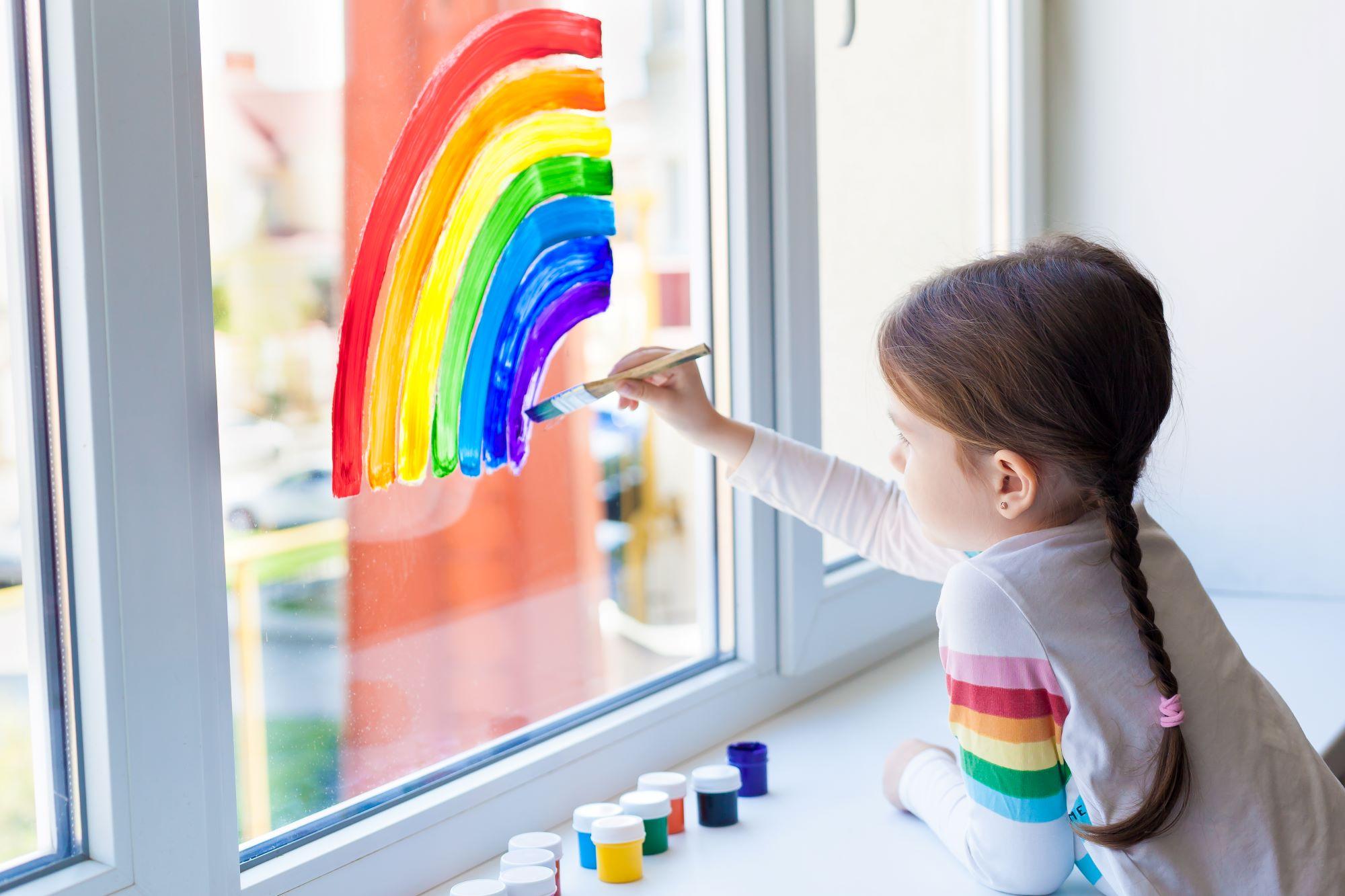 A little girl paints a rainbow on a window