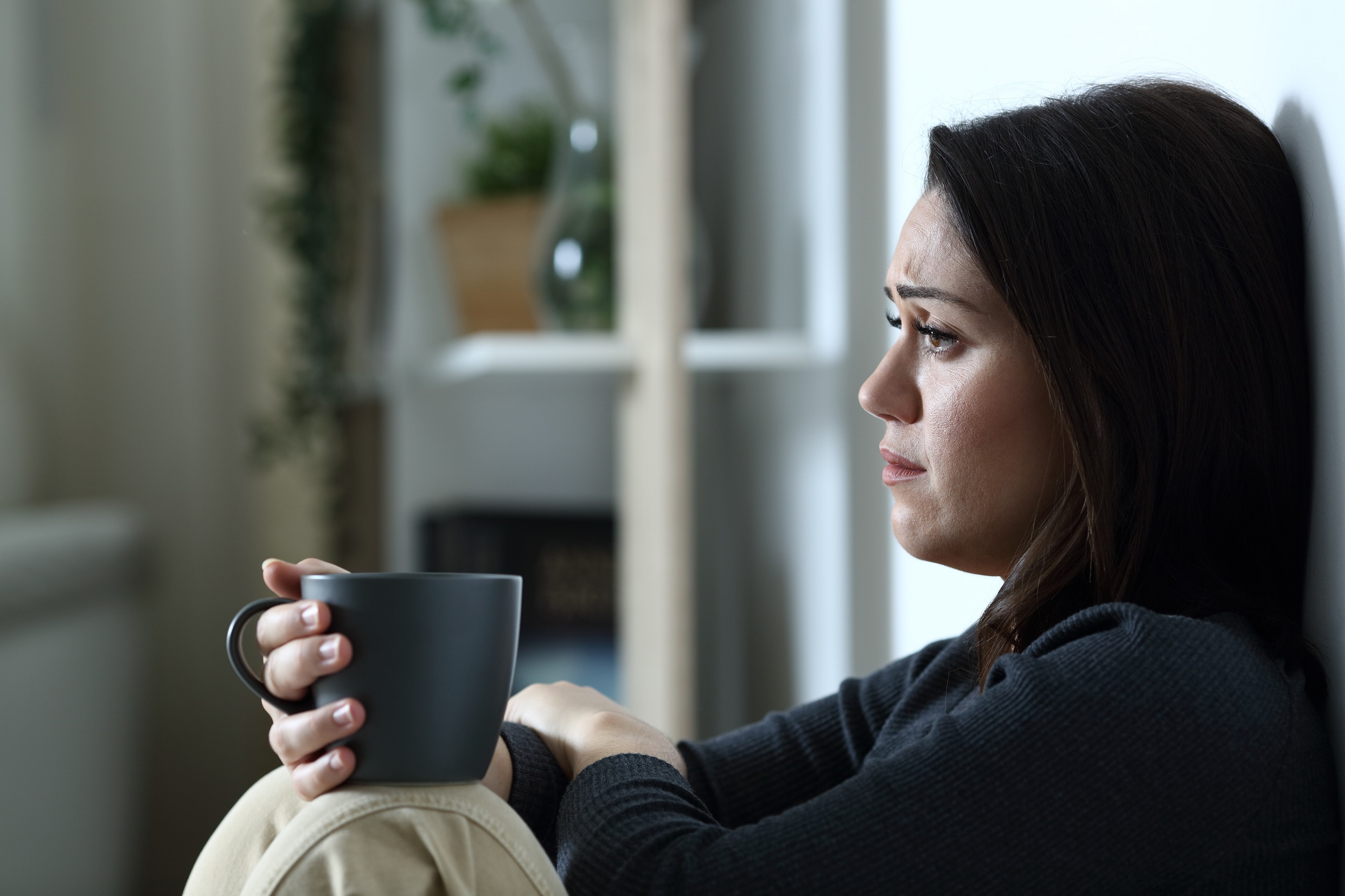 Sad woman with coffee cup looks away alone at home in the night