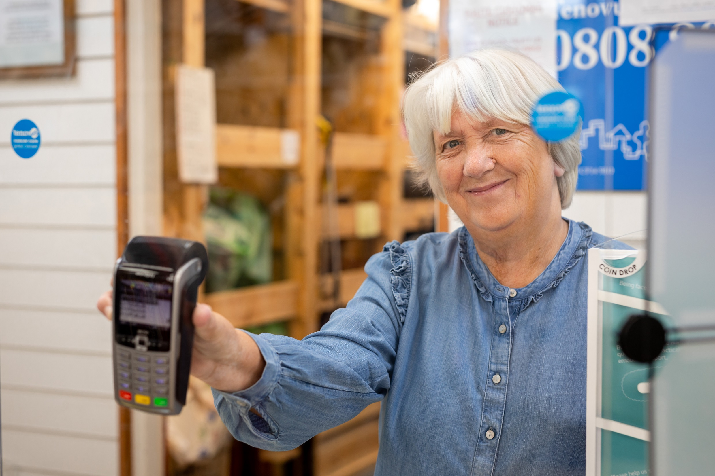 Tenovus Cancer Care charity shop volunteer smiles and holds up contactless payment terminal to a perspex protective screen