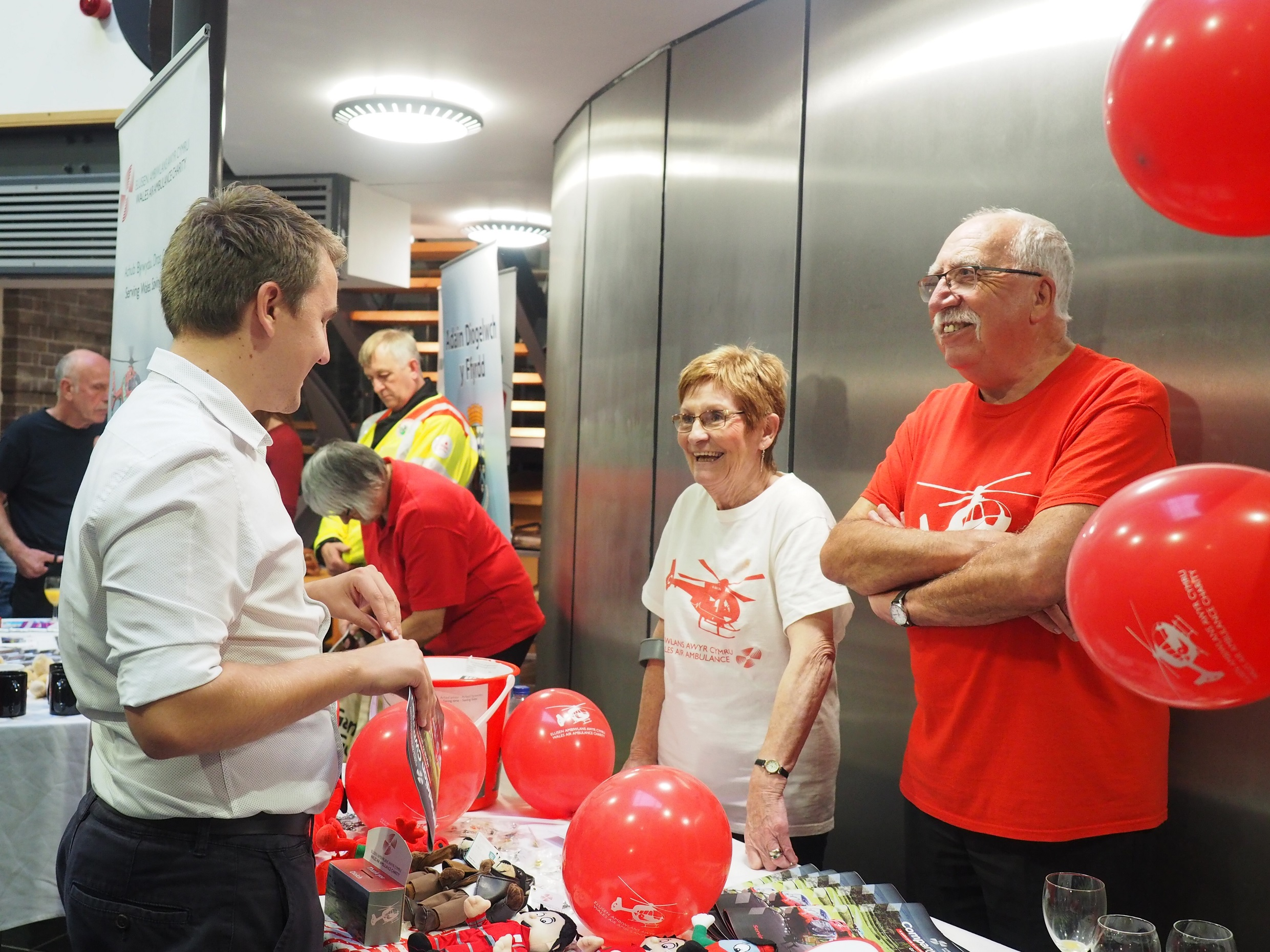 Wales Air Ambulance volunteers man a publicity stand with balloons and charity merchandise at an event. A man and a woman are wearing red and white charity t-shirts and laughing with a visitor