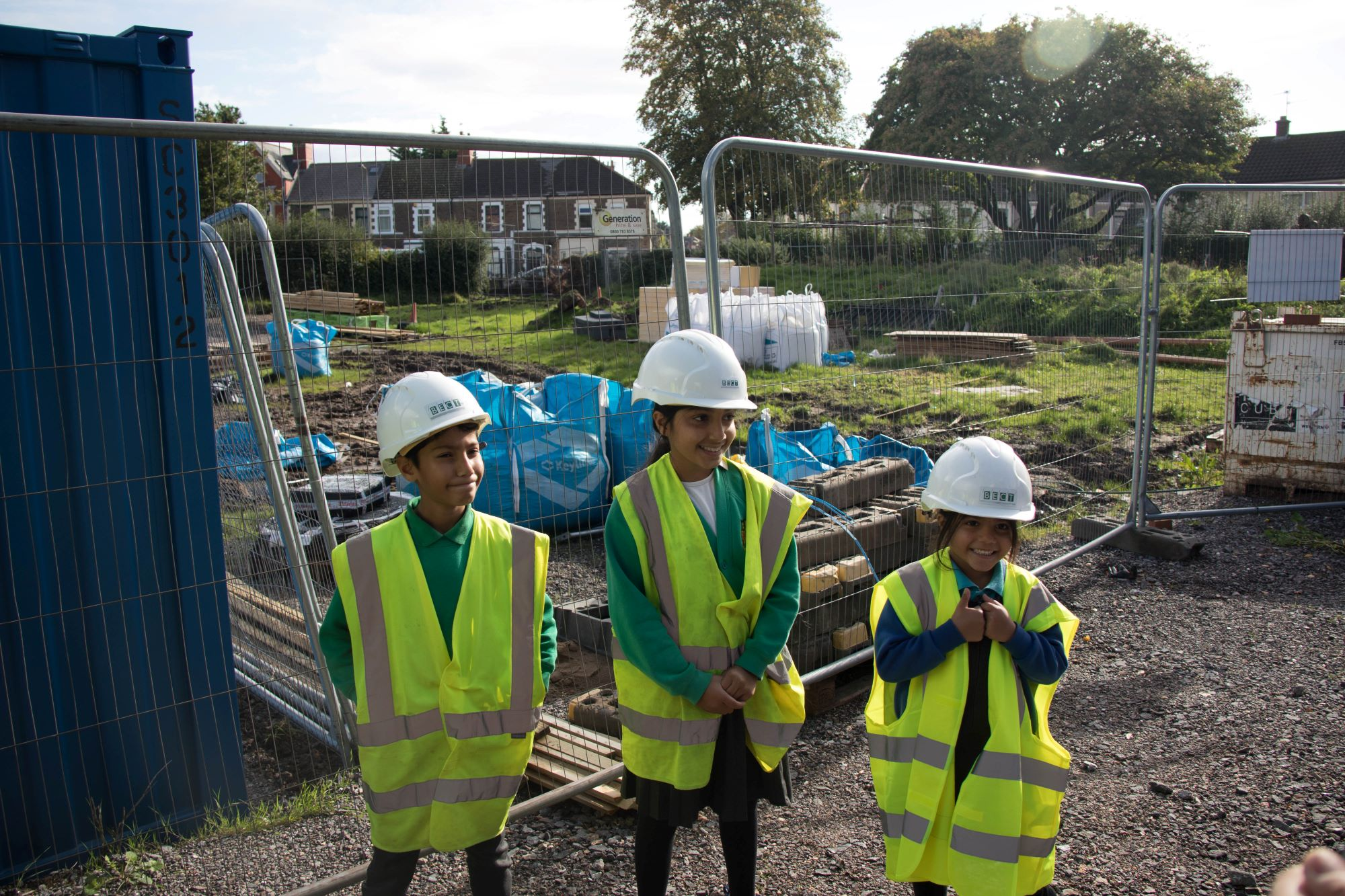 Children in hi vis vests and building helmets standing next to the site of the new Grange Pavilion, recipients of a Landfill Disposals Tax grant