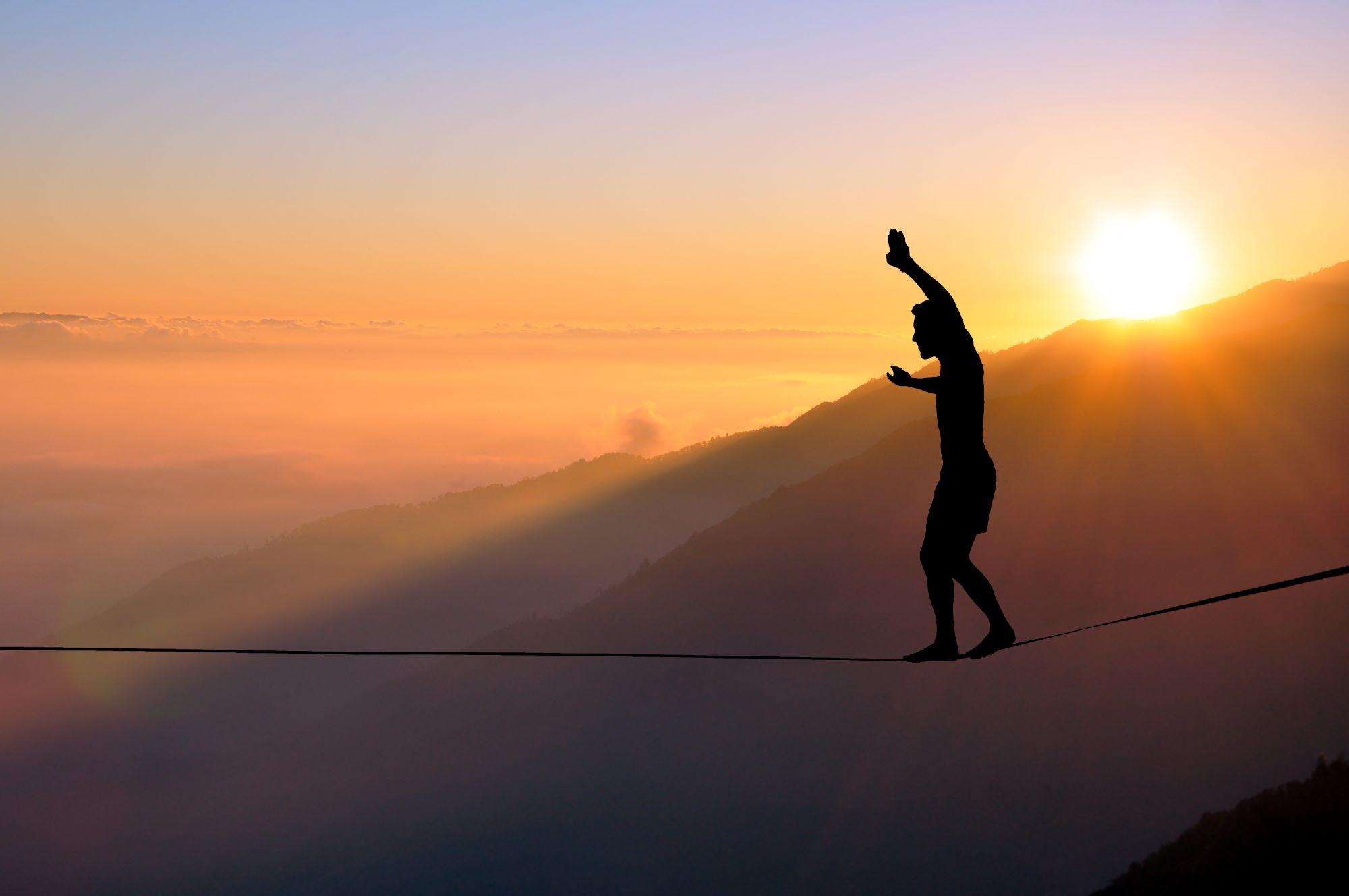 Man walking tightrope above a ravine at sunset
