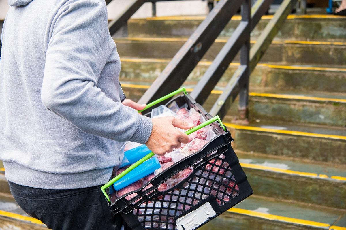 Man in grey hoodie caries basket of food essentials up some stairs