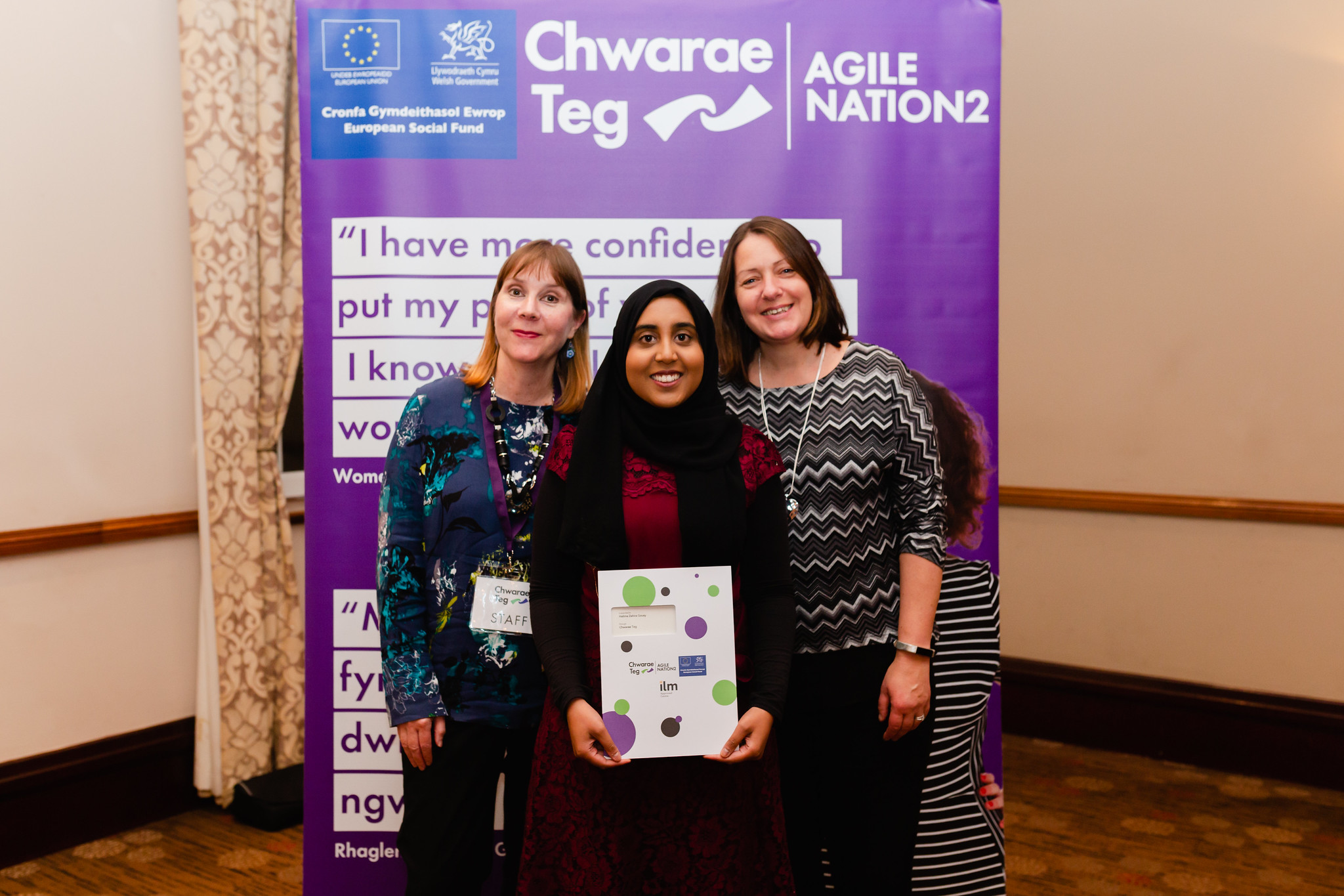 Zahira Gousy graduating from the ILM career devlopment programme, with members of the Chwarae Teg team.