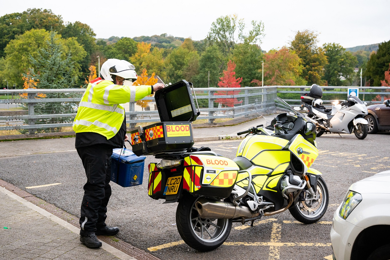 Volunteer in high vis places important NHS materials on the back of his motorbike. The bike is high vis and has the word BLOOD