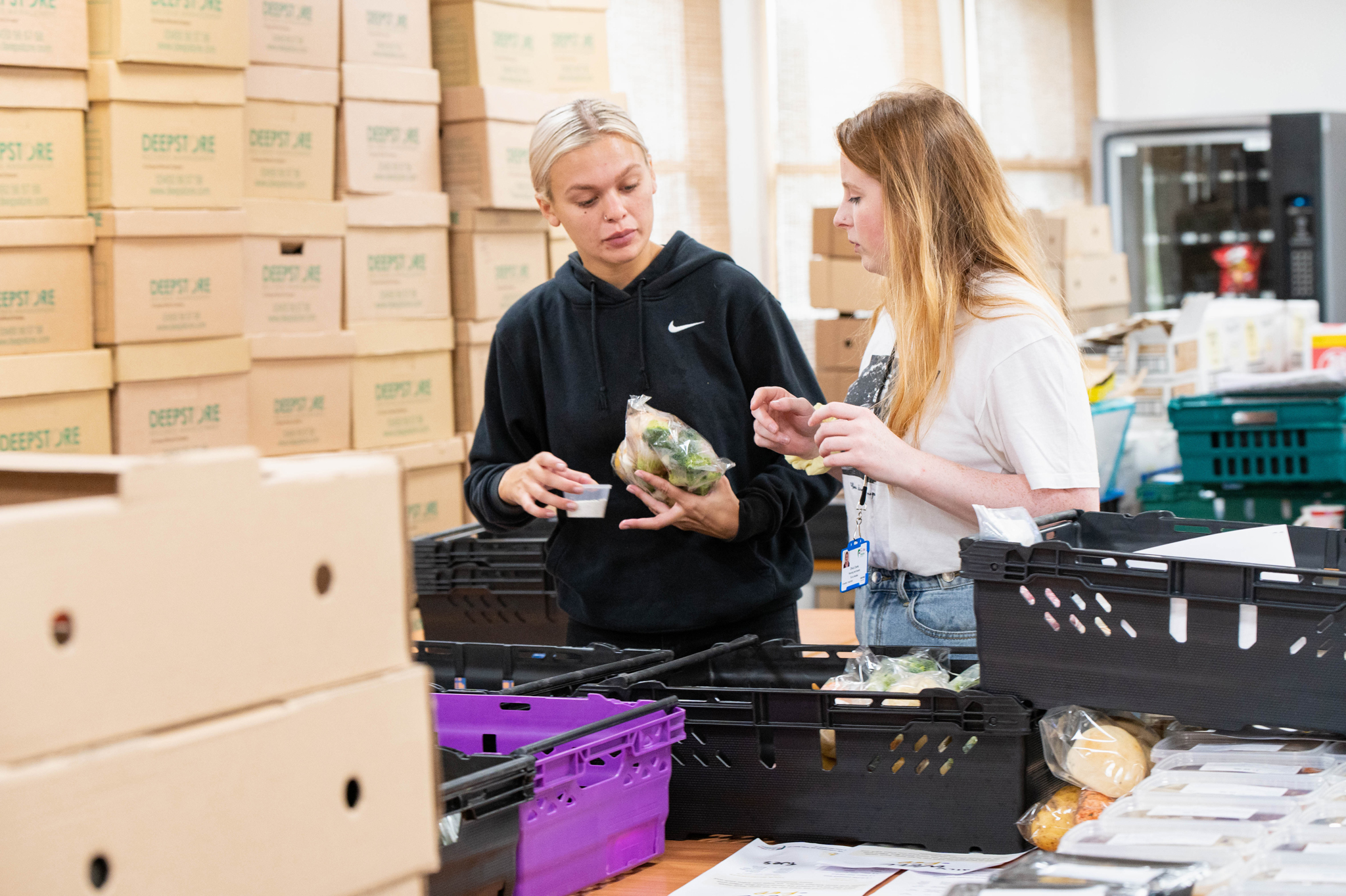 Two young people volunteer at food distribution centre