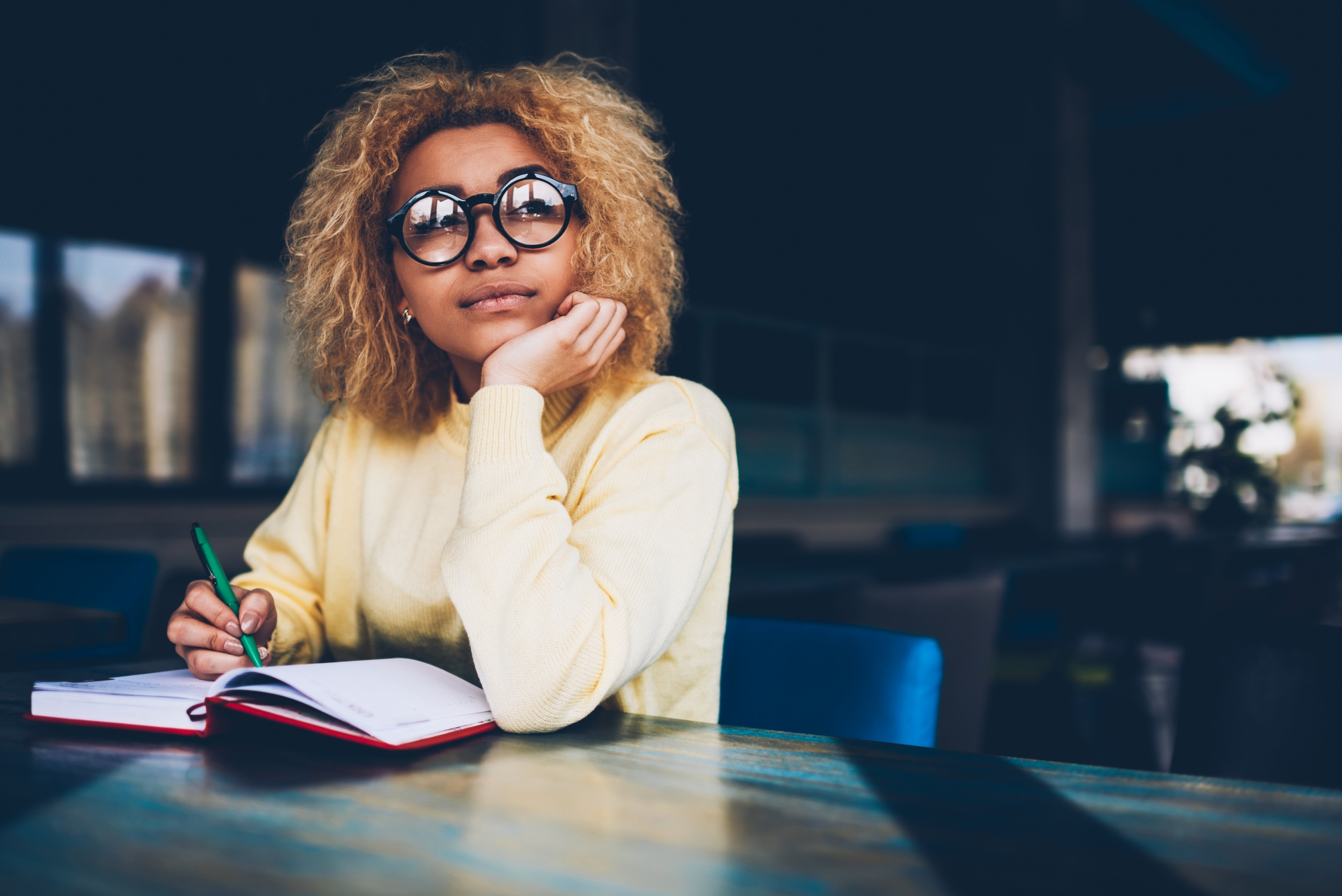 young woman thinking of resolutions writing in notepad