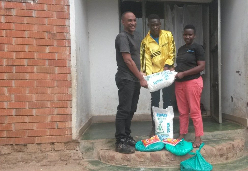 Project beneficiary Doreen accepts her delivery of poshu (maize flour), beans, rice and soap from Barry Atugonza (left) who is the Project Coordinator for AGLMUK