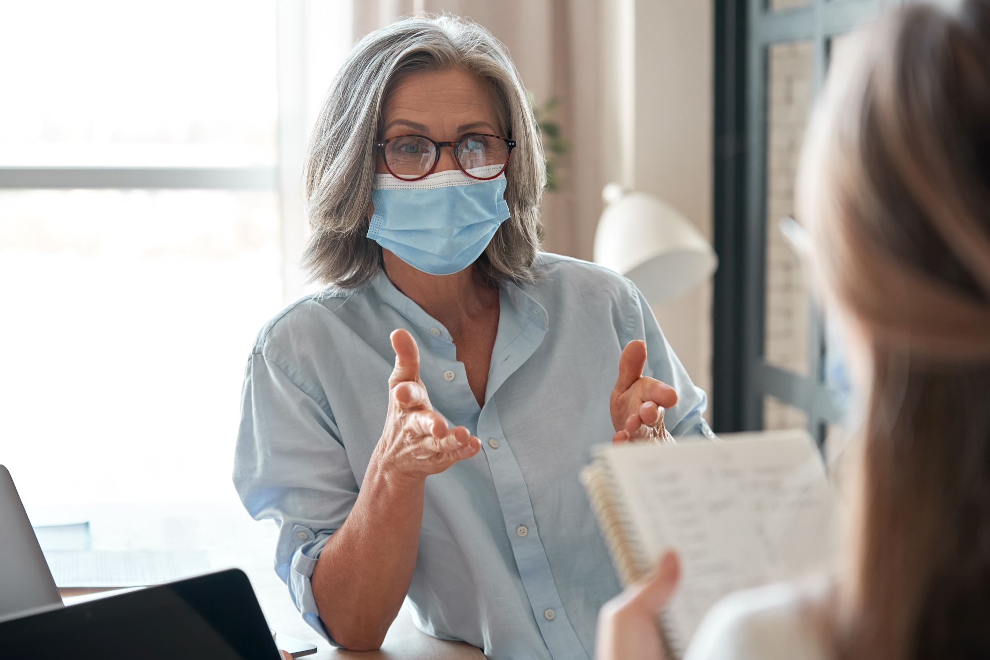Older female manager wearing face mask training young worker