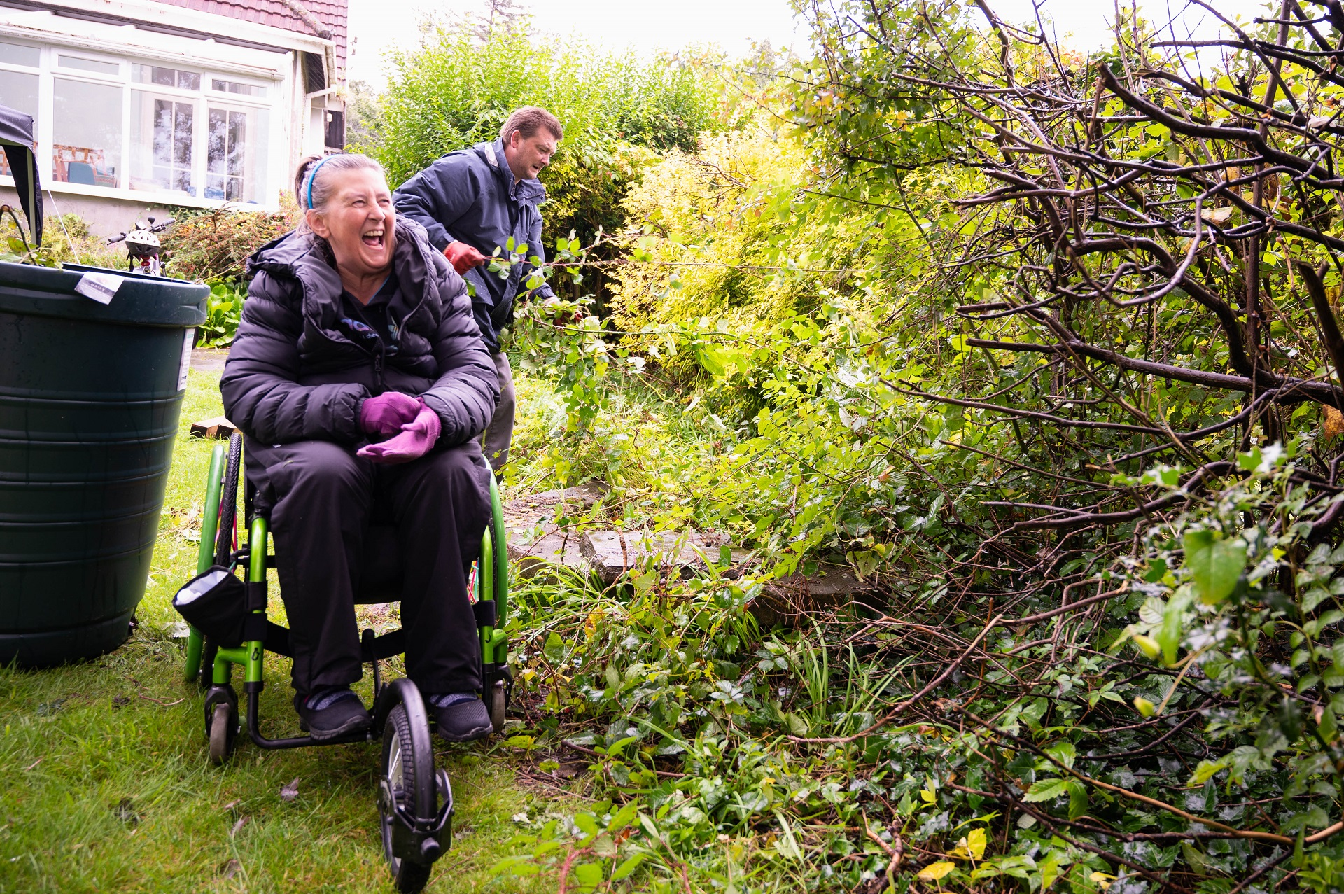 Volunteers gardening for wellbeing, a woman in a wheelchair laughs while weeding with a fellow volunteer