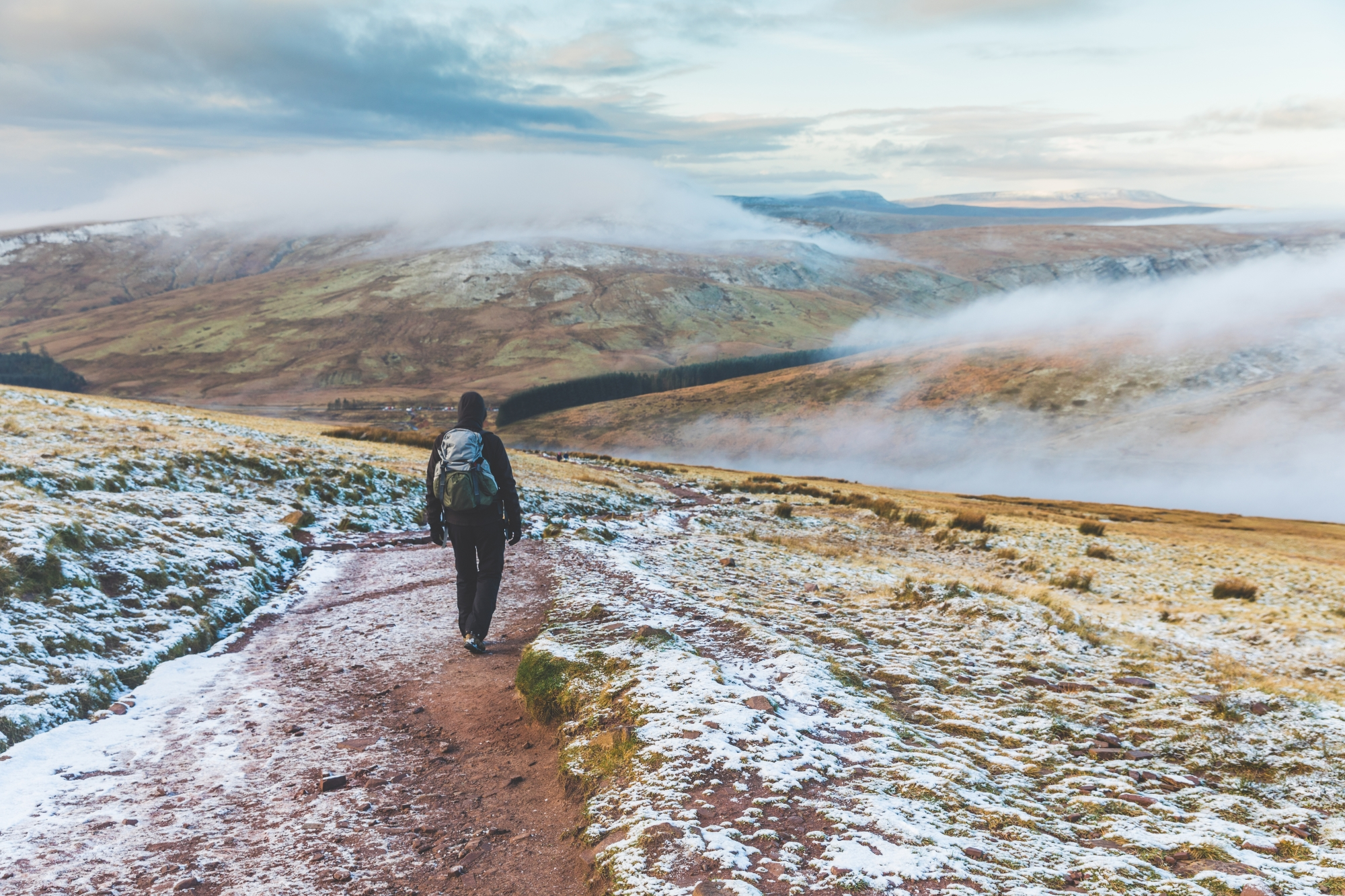 Man walking on snowy hills in Wales