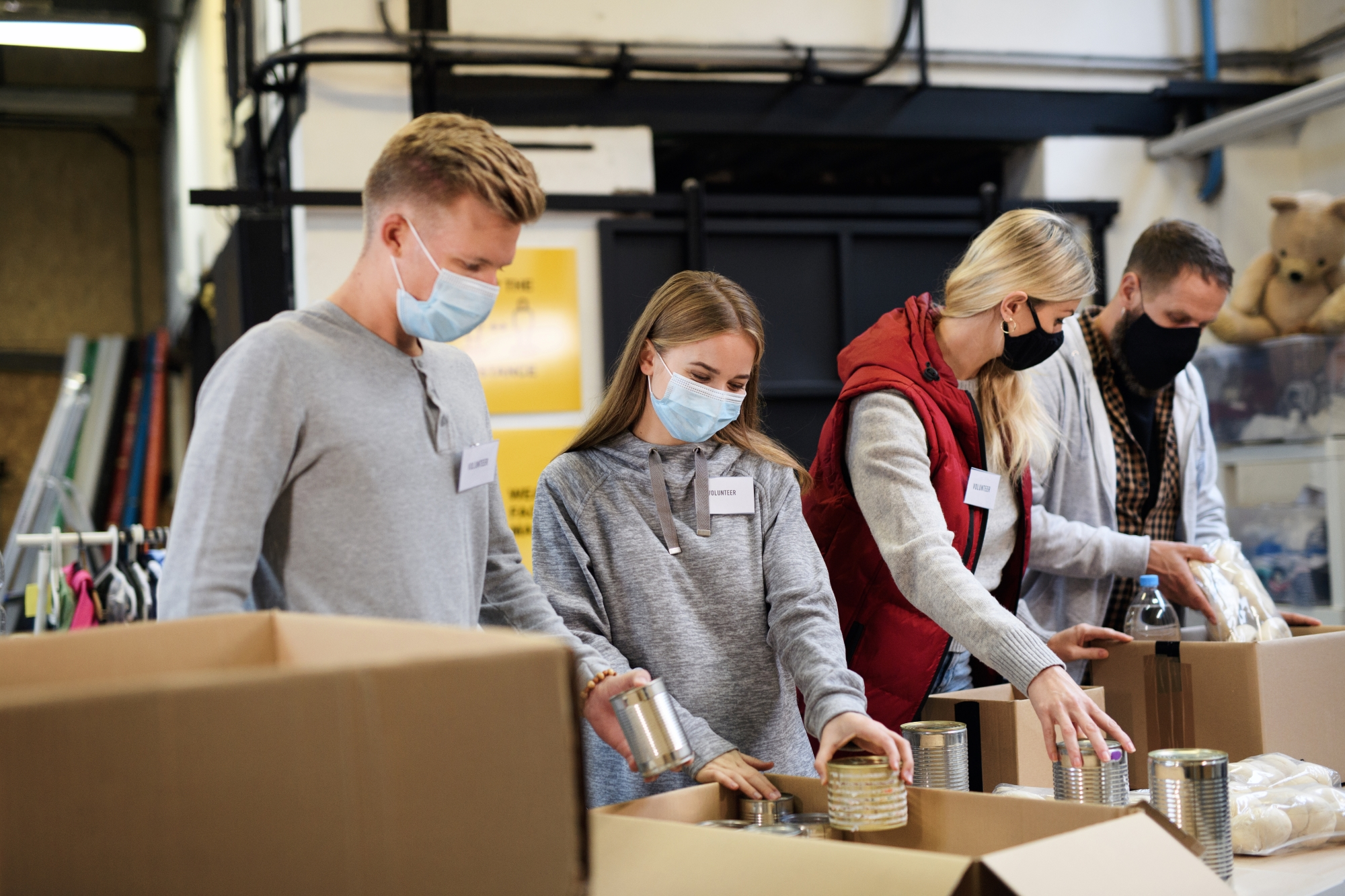 Group of volunteers in facemasks volunteer at foodbank
