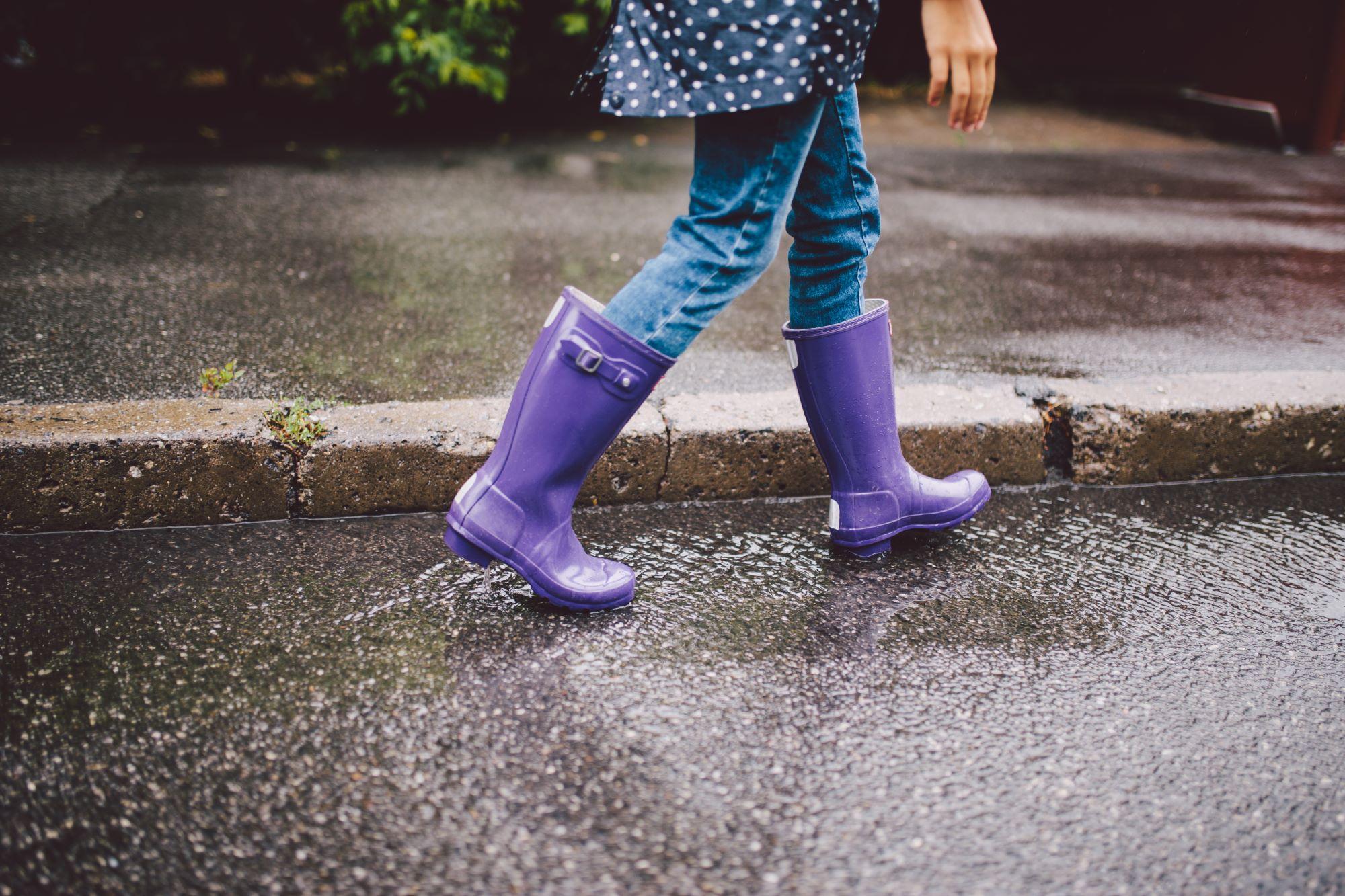 Girl walking down pavement in purple wellies
