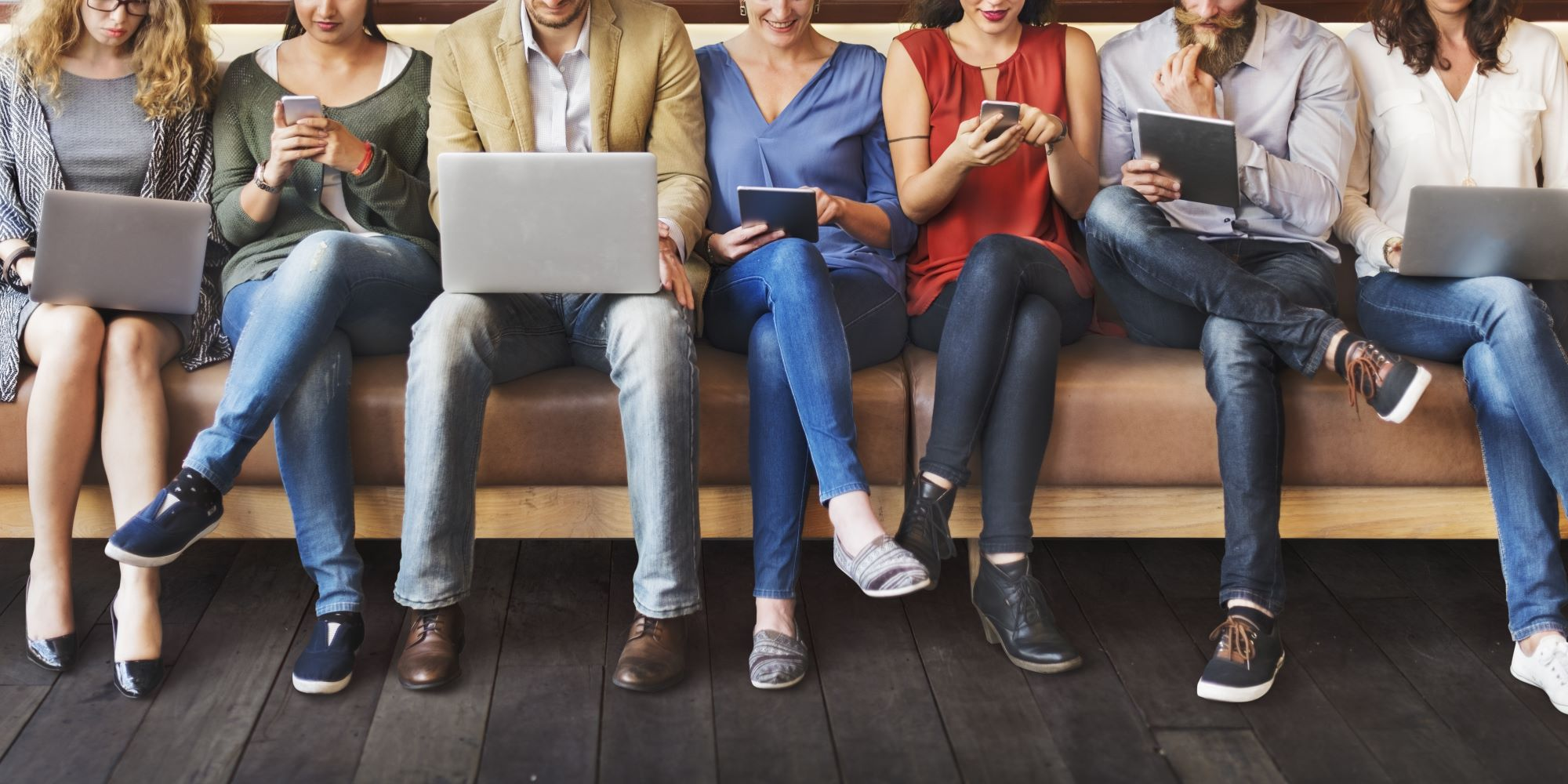 people sit in a line using their various digital devices