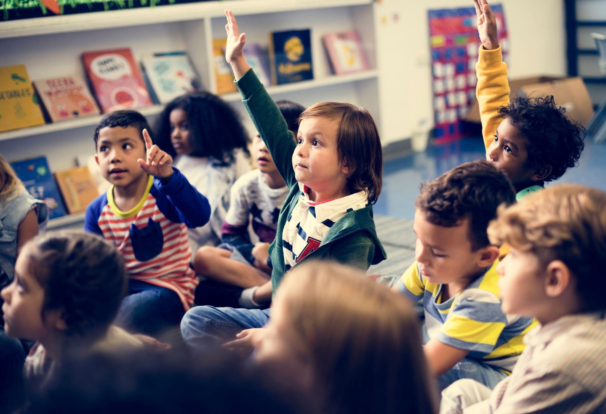 children in classroom, one with hand up