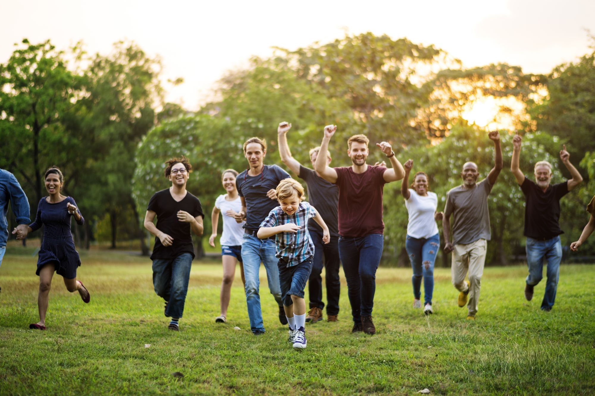 Group of people walking and running playfully in the park