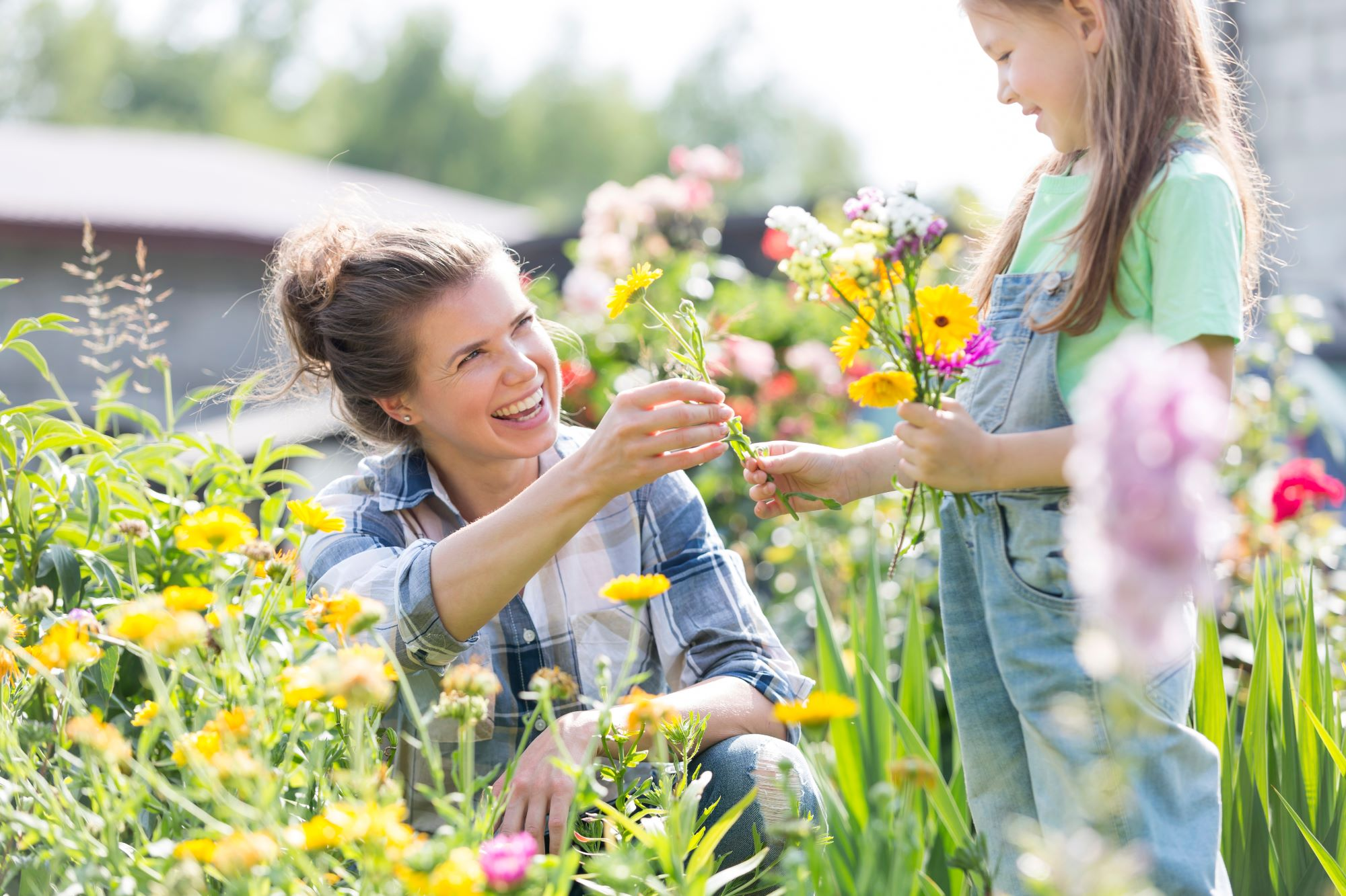 Woman handing flowers from garden to young girl