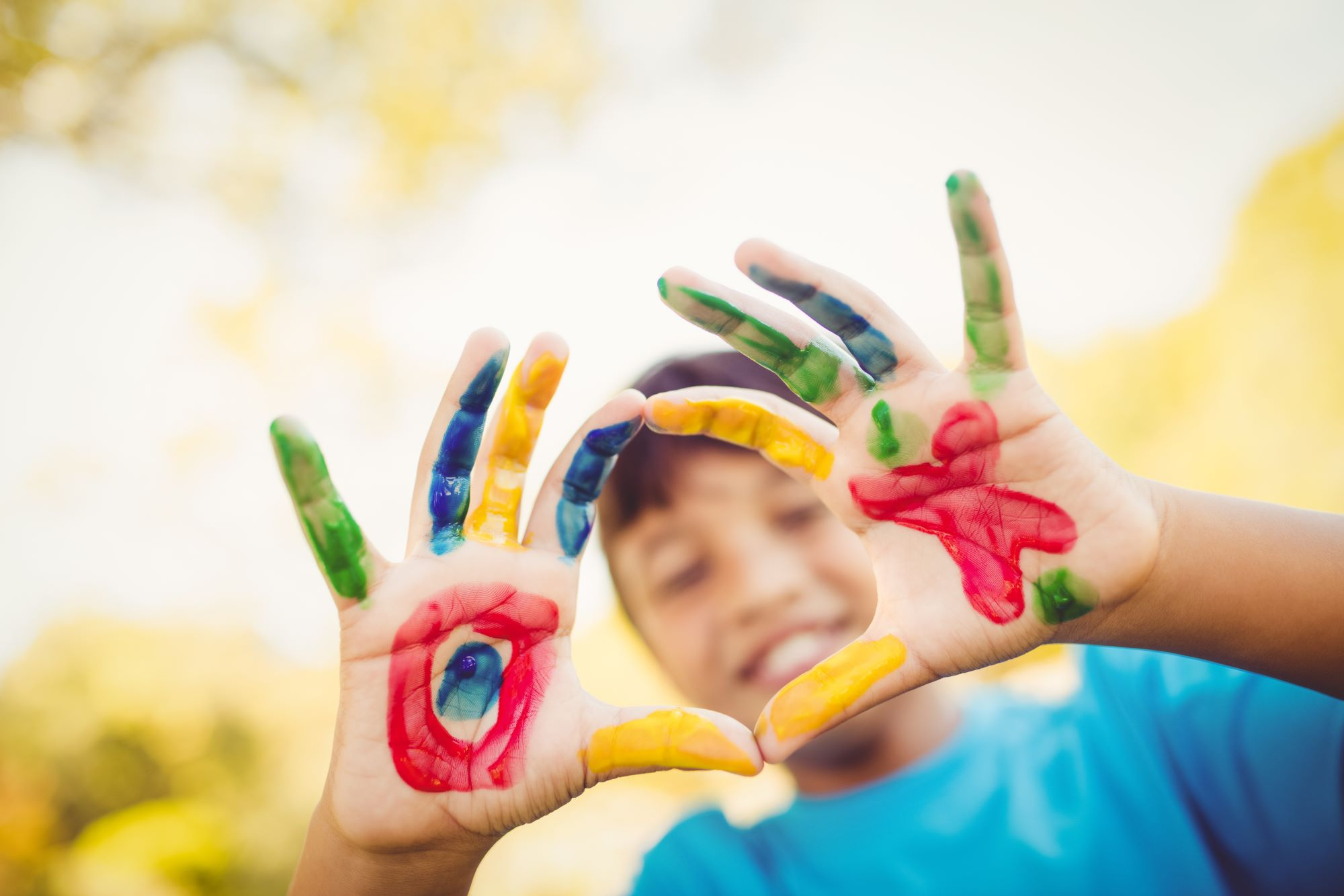 Boy making a circle to the camera with his hands painted in a park