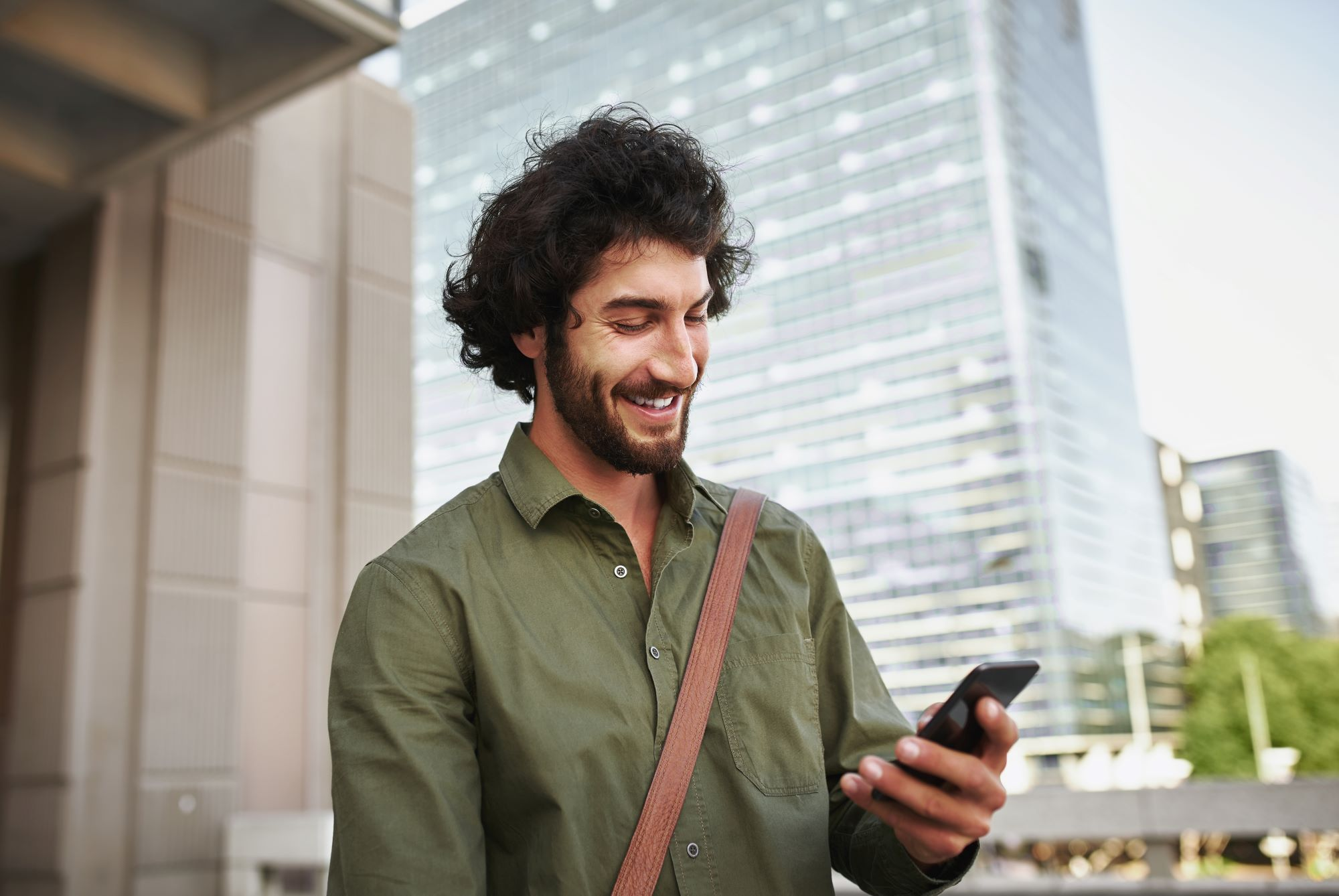 Man smiling as he does the census on his smartphone