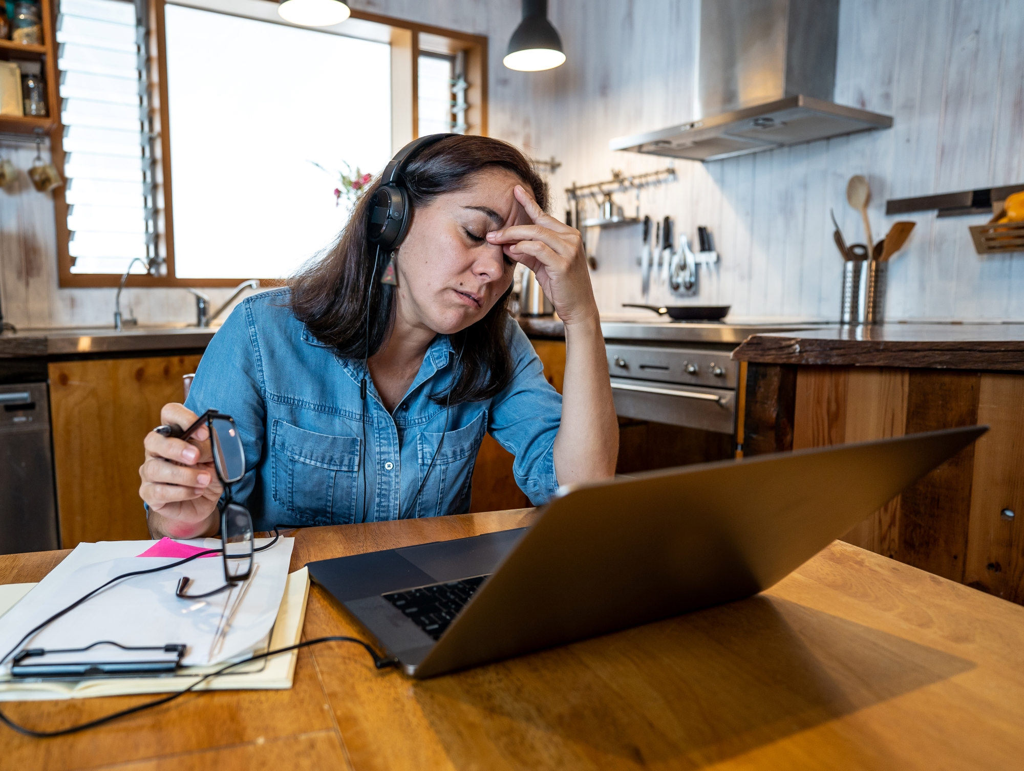Stressed woman working from home, fingers on temple, laptop at kitchen table with papers everywhere