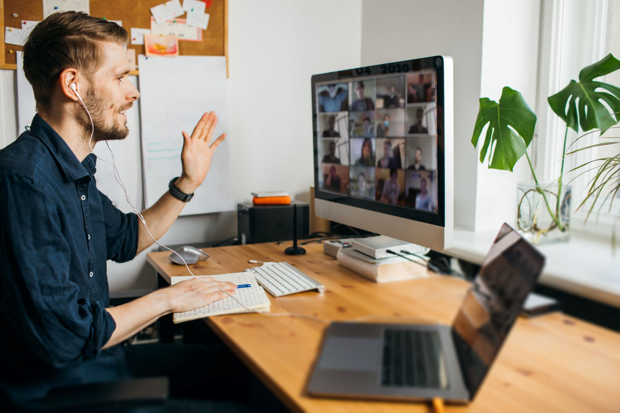 man waves at screen during online meeting