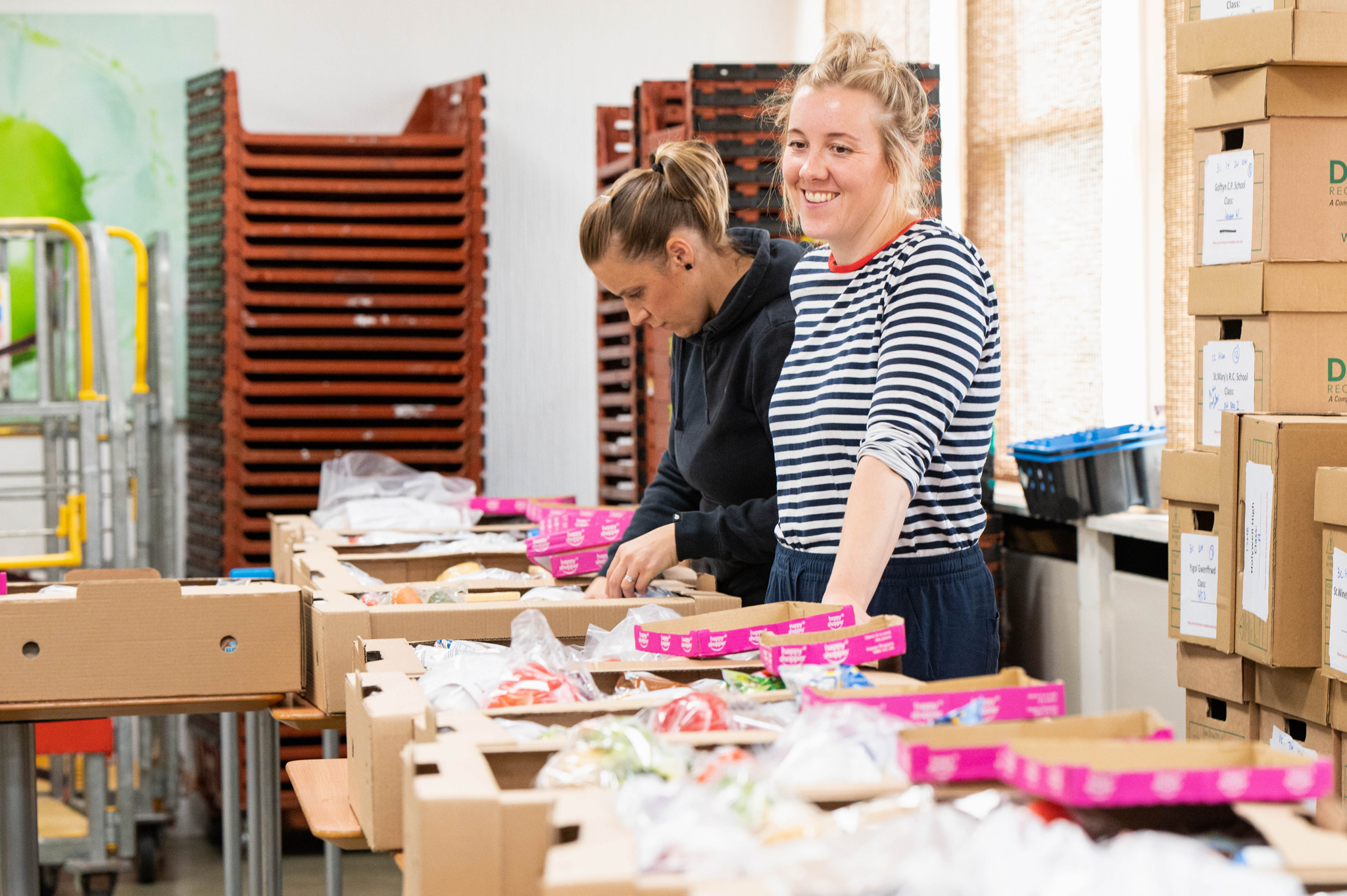 Two volunteers prepare food boxes for the community, one smiles broadly