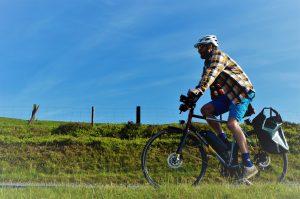 A man rides a bike past a field