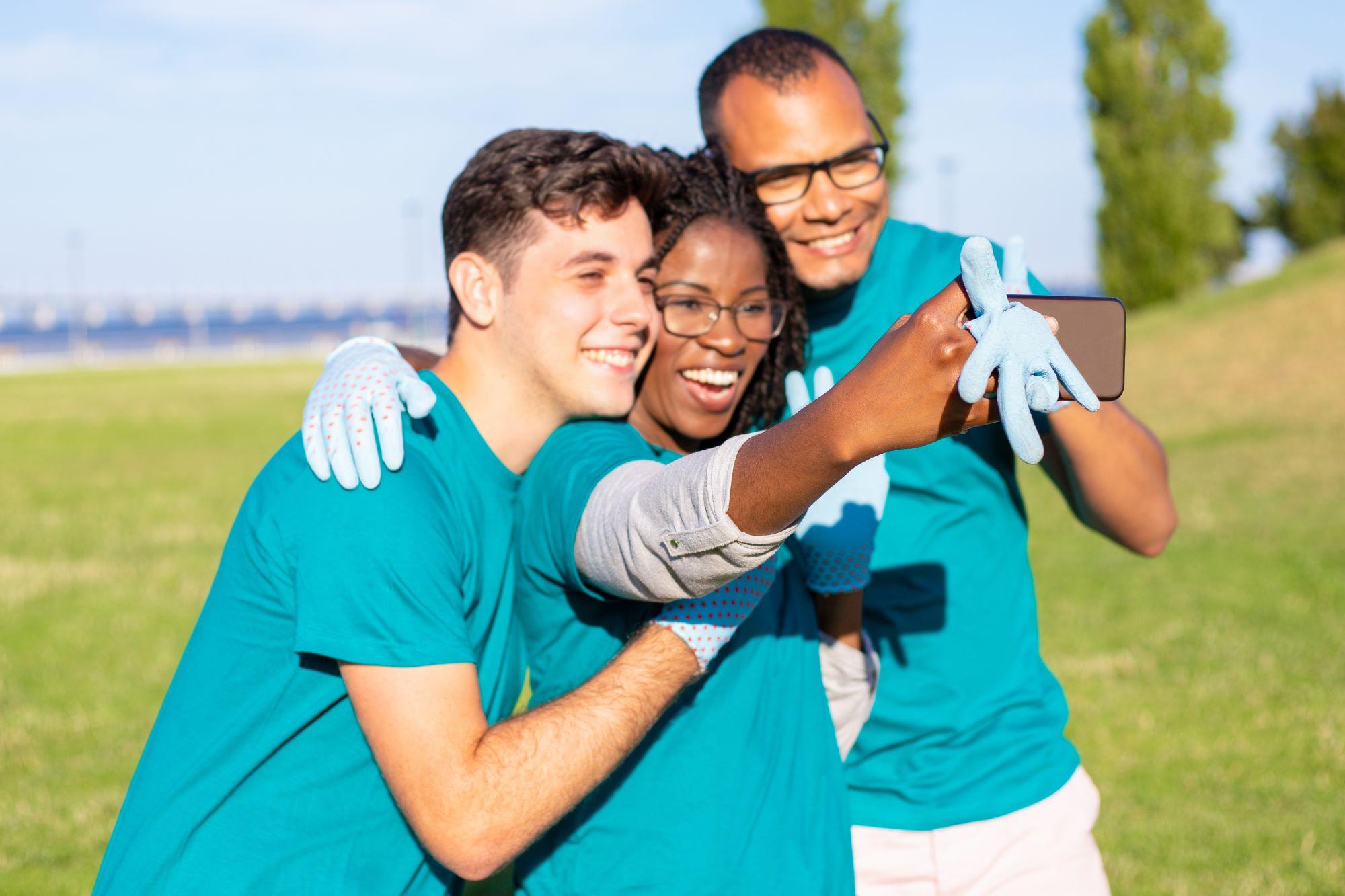 three volunteers taking a selfie outside
