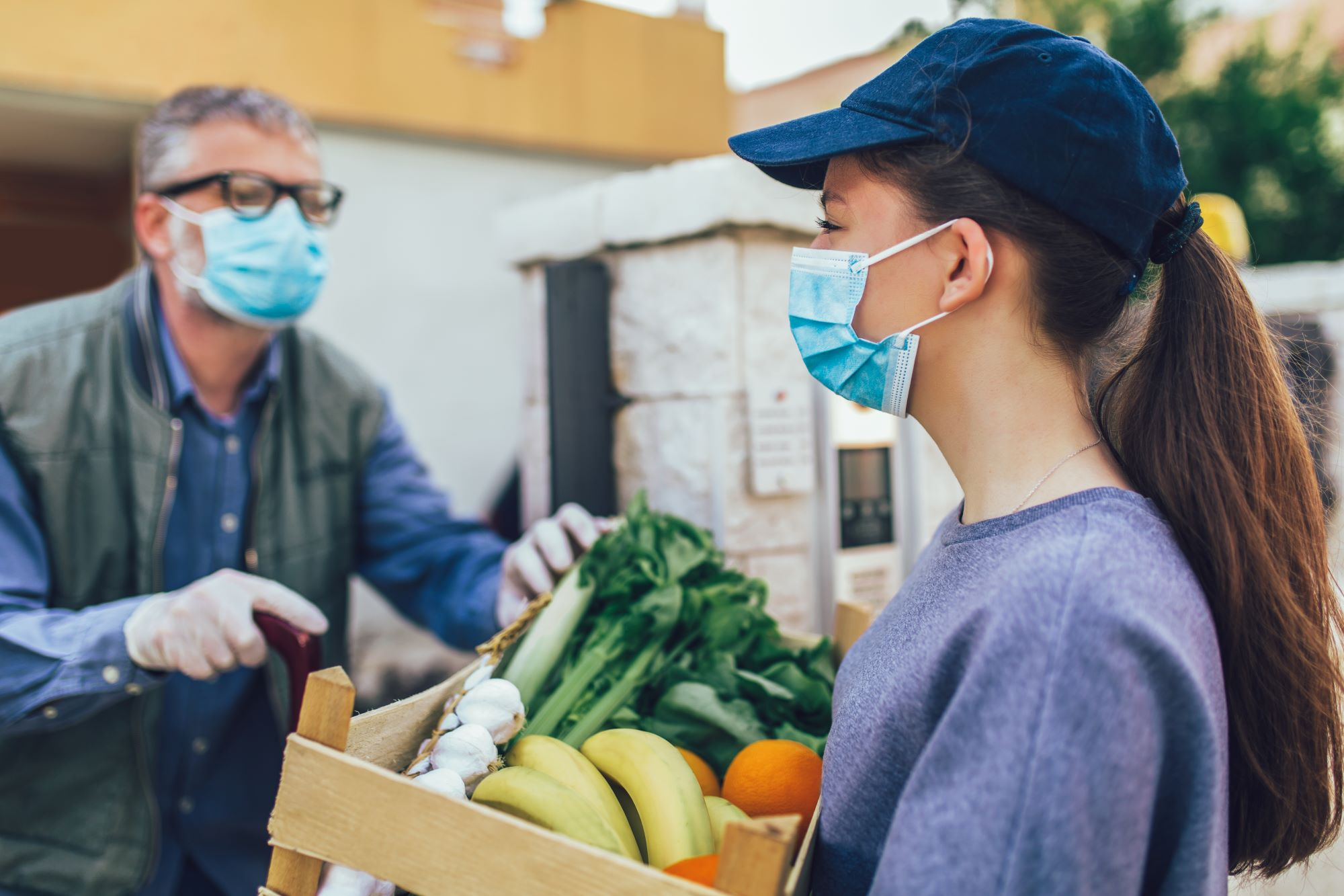 young volunteer delivers food basket to older neighbour