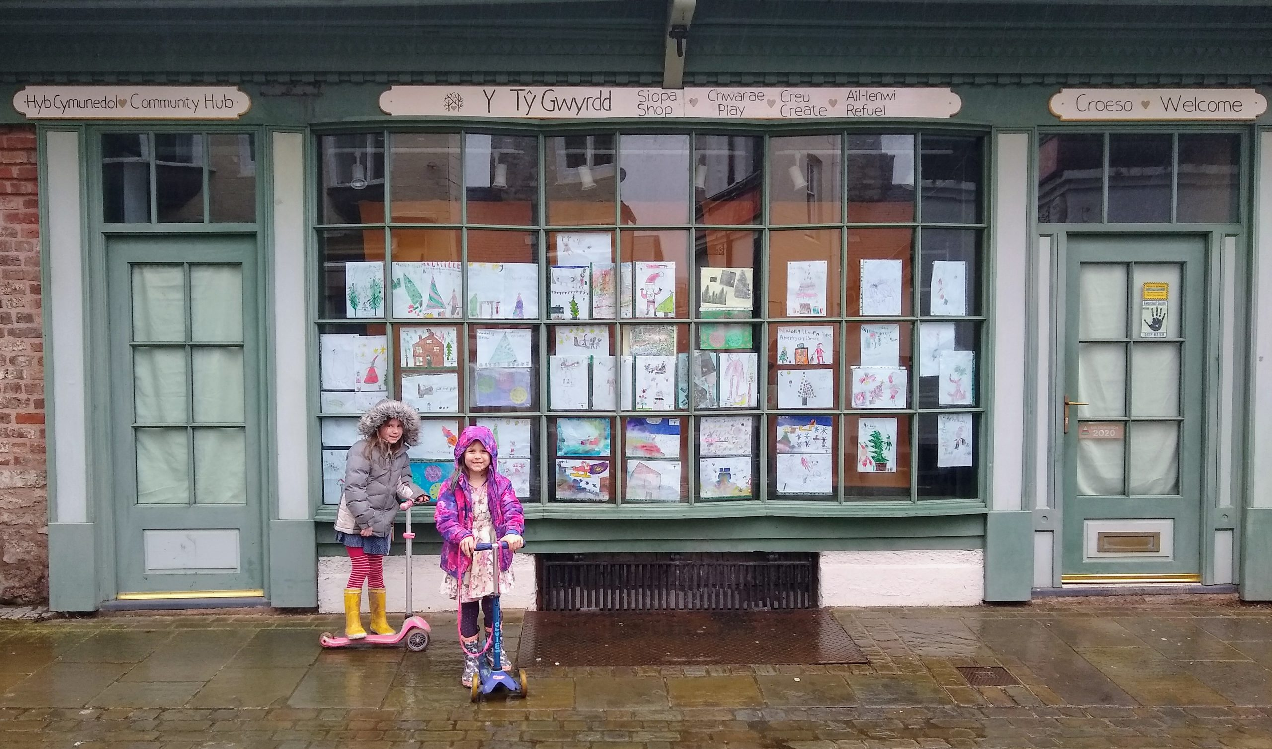 Children stand in front of Y Tŷ Gwrydd's front window