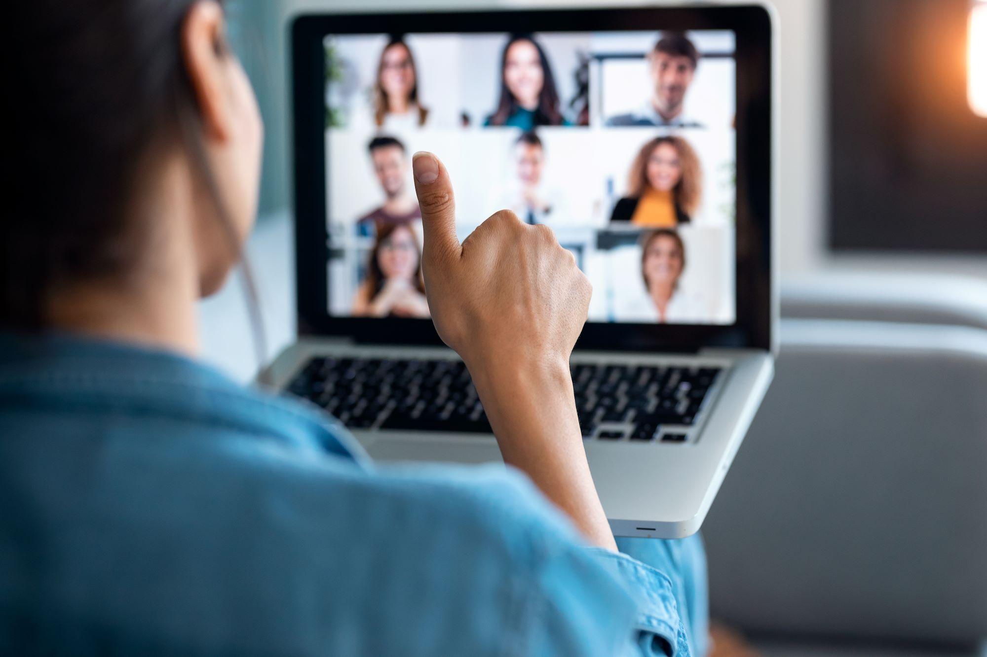 Woman gives thumbs up to virtual meeting