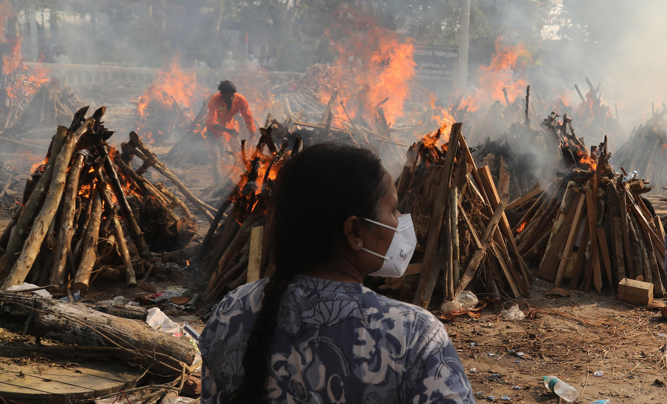 In India a woman in a face mask stands in front of dozens of lit pyres
