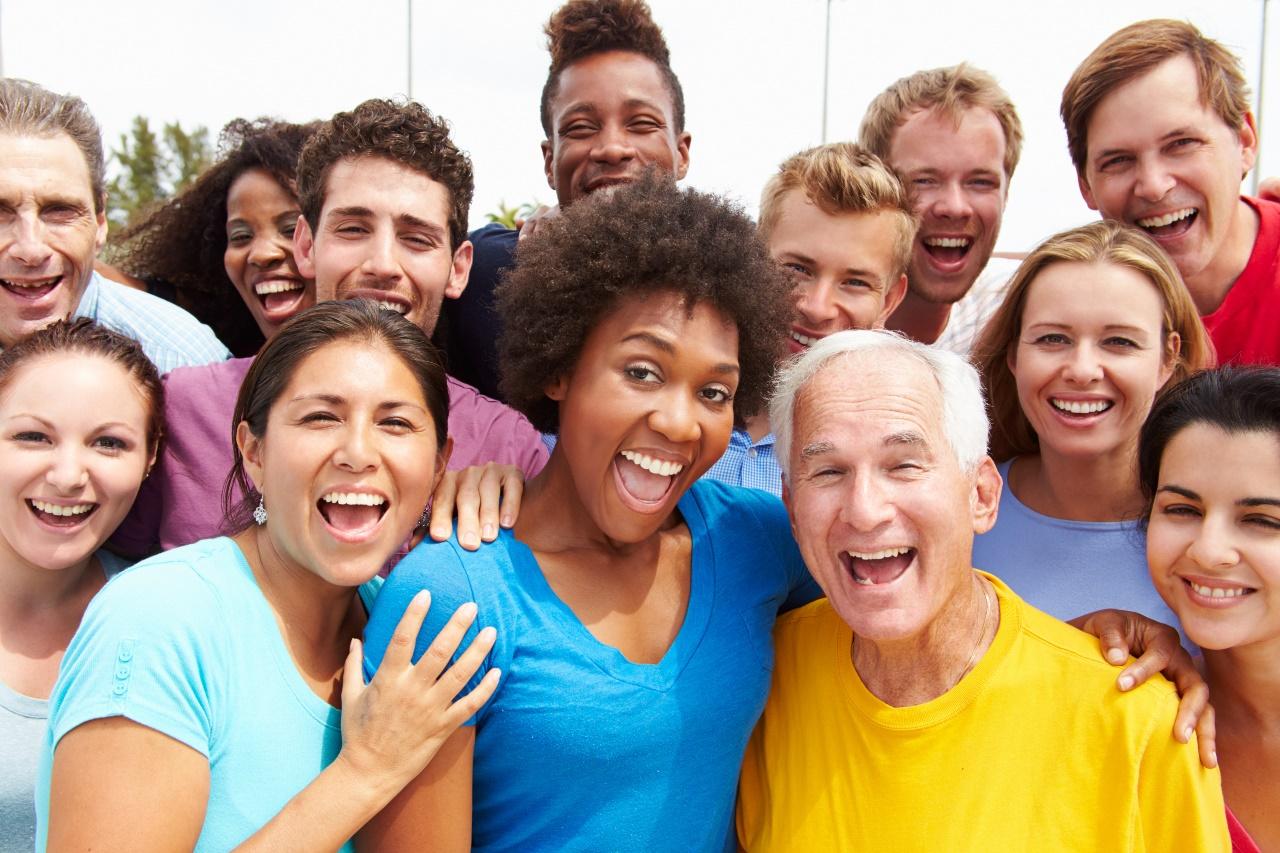 Group of smiling volunteers stand together shoulder to shoulder