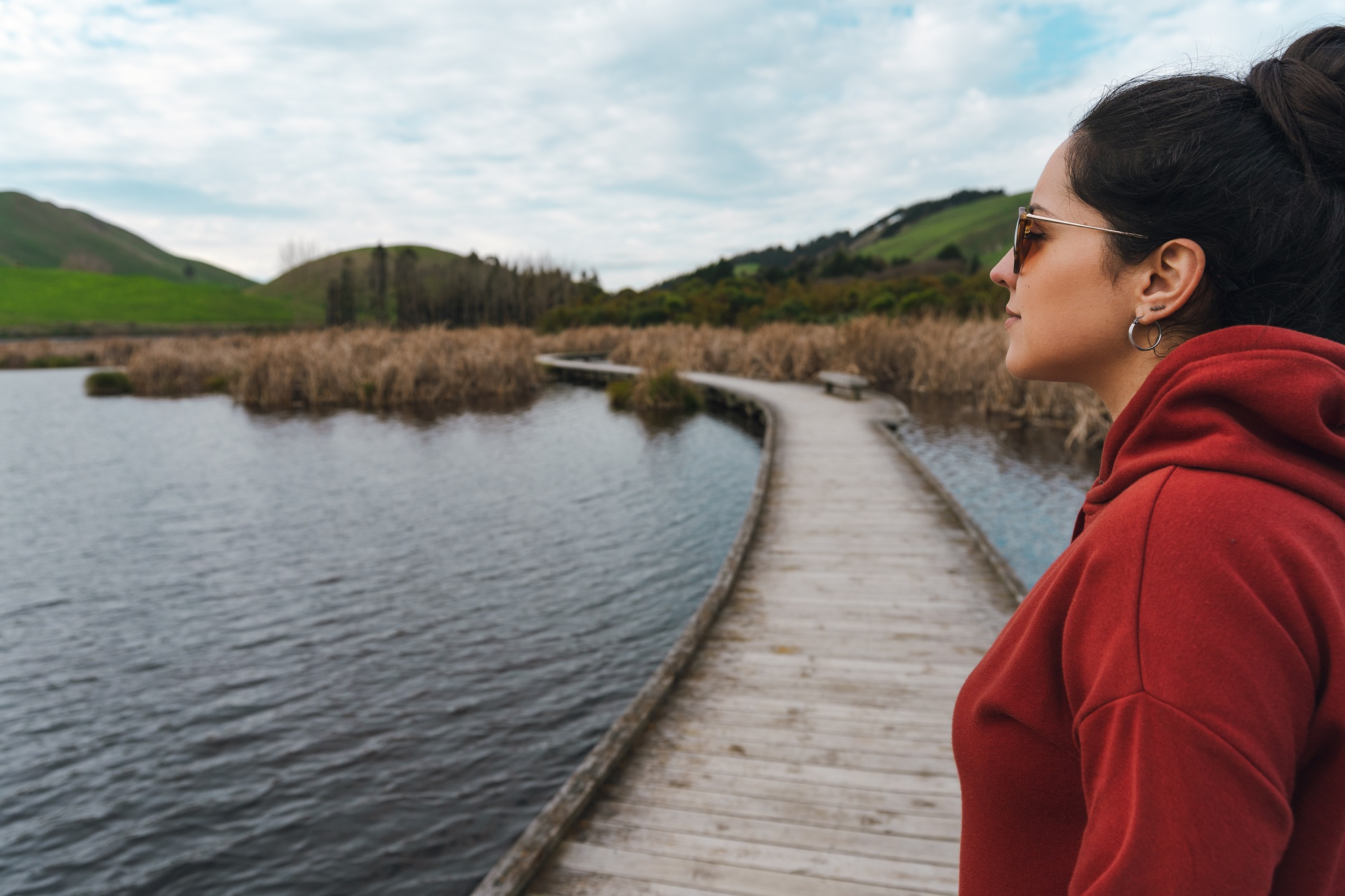 Brunette woman wearing hoodie and sunglasses stares out across some wetlands
