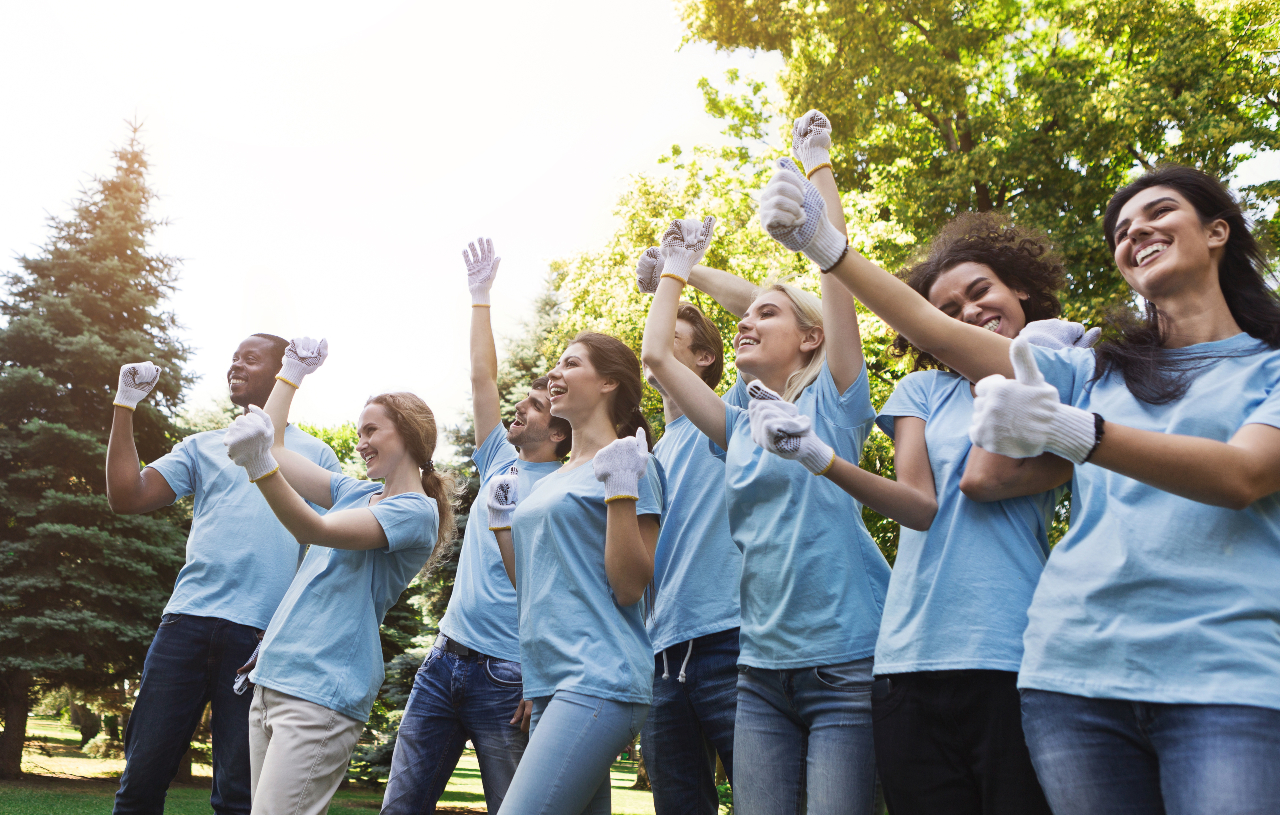 A group of happy looking volunteers stand together outside, raising their arms and smiling