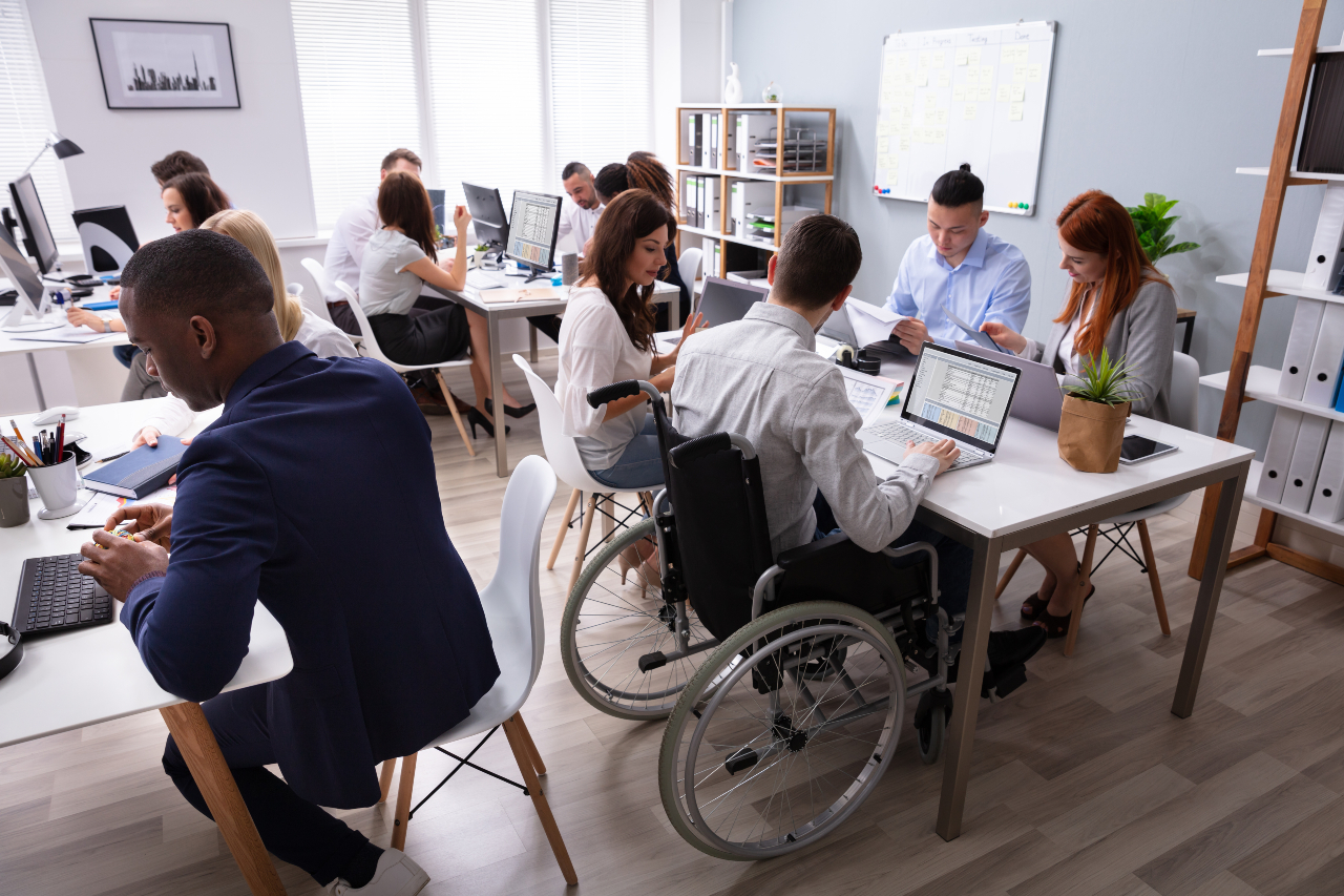 Group of people sit around tables in open plan office