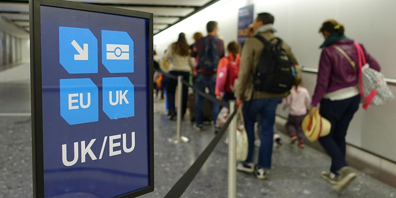 People walking through customs past EU nationals sign