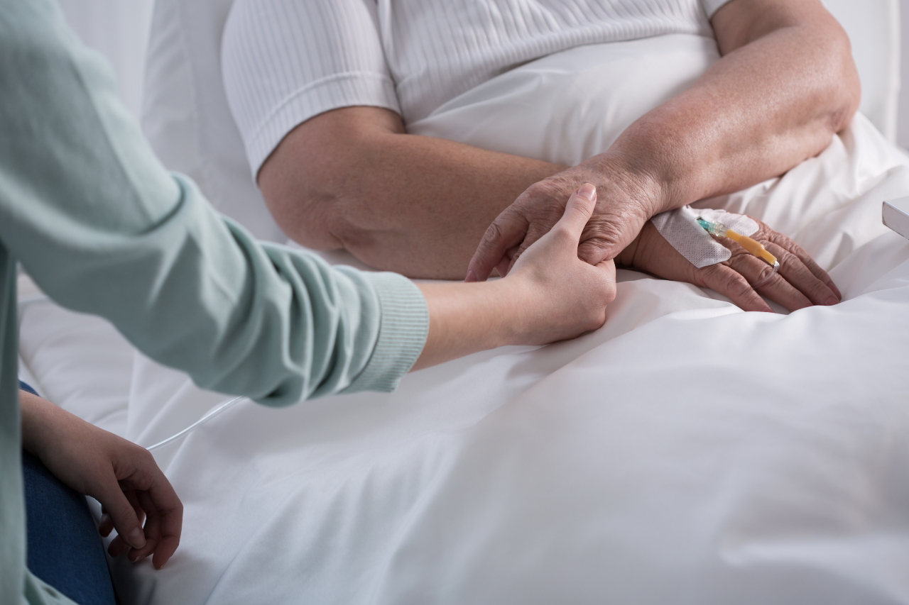 Two people hold hands over a hospital bed